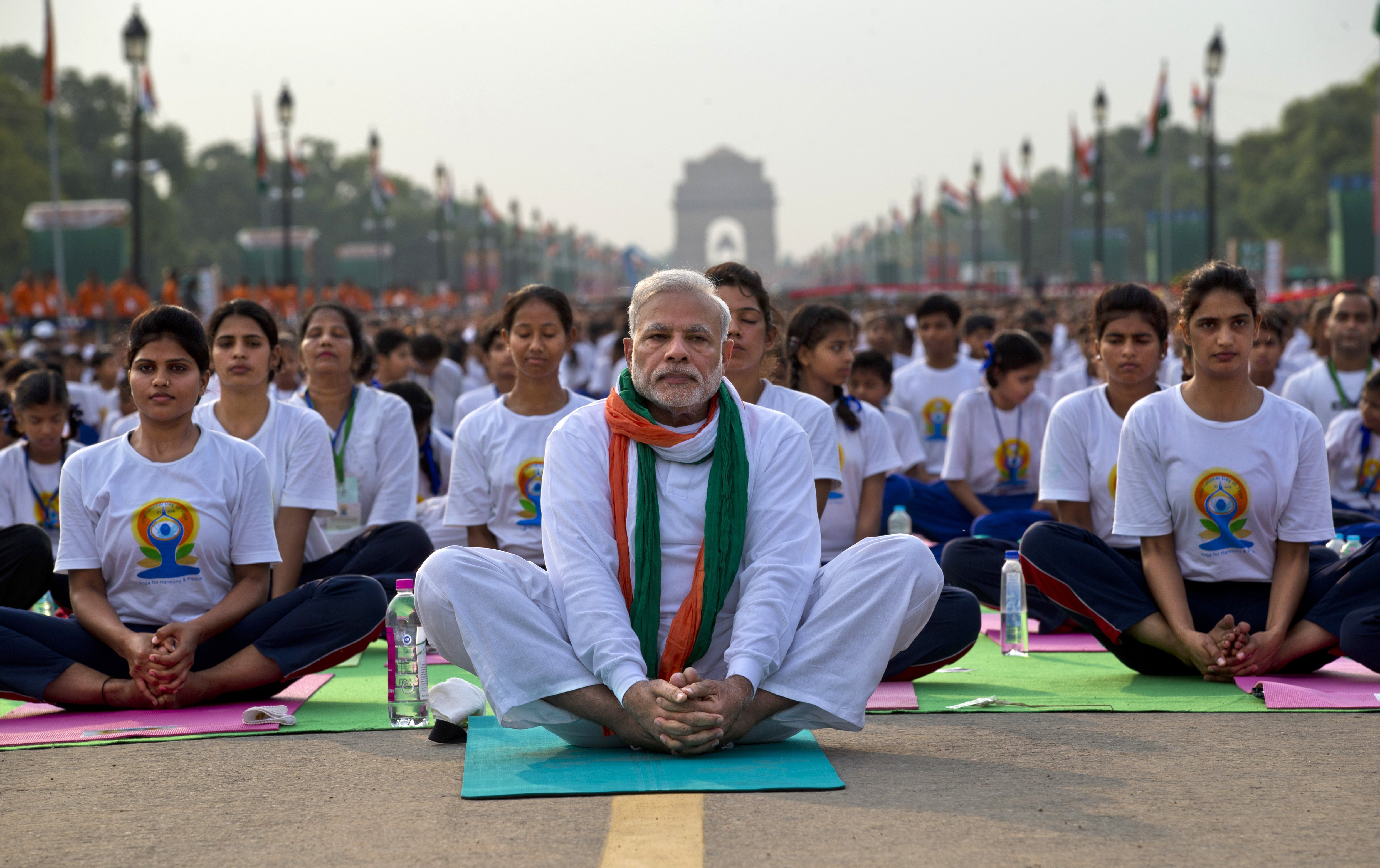 Indian Prime Minister Narendra Modi sits on a mat as he performs yoga along with thousands of Indians on Rajpath, a boulevard in New Delhi, June 21, 2015.