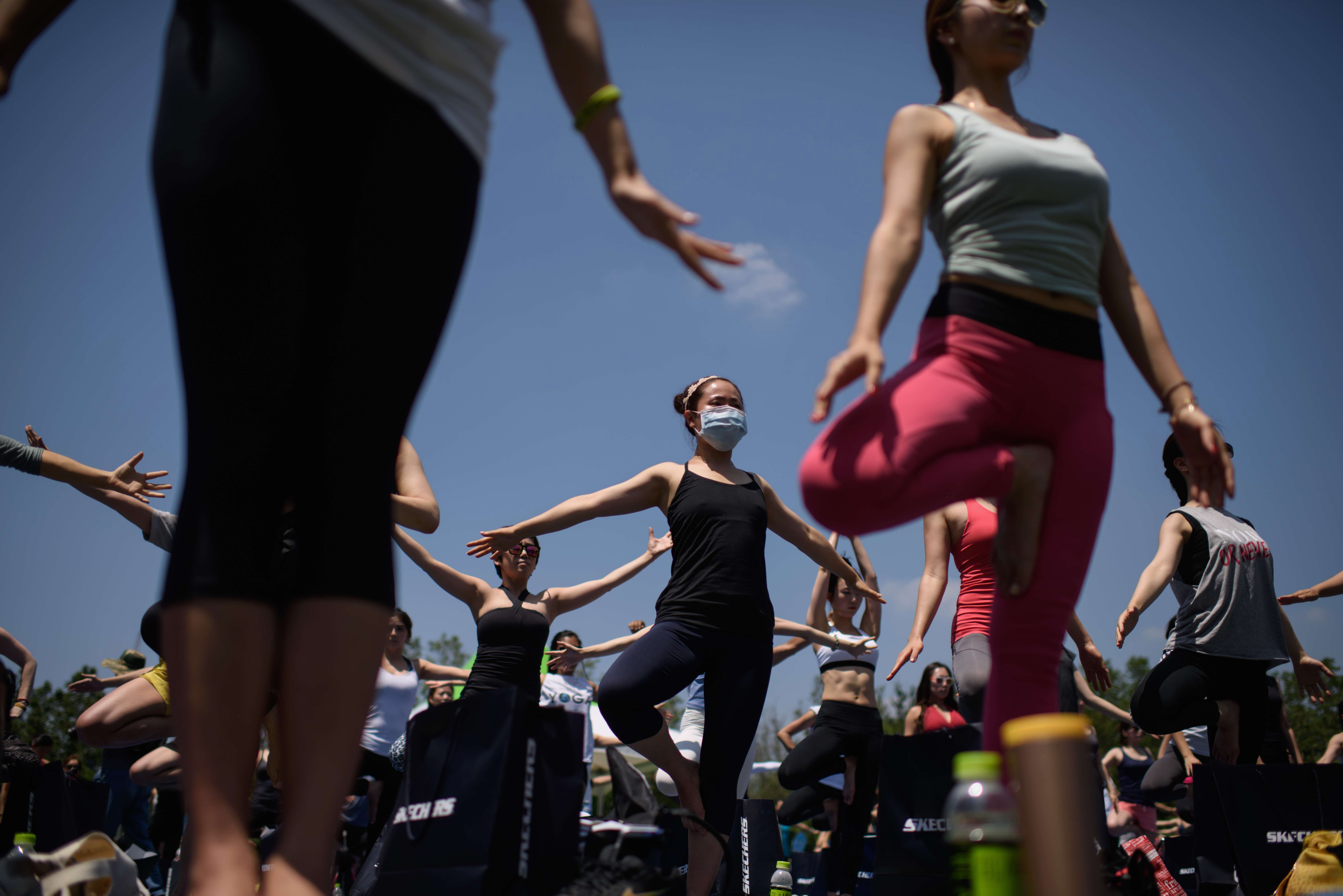 A woman wearing a mask takes part in the International Yoga Day event in Seoul, South Korea, on June 21, 2015.