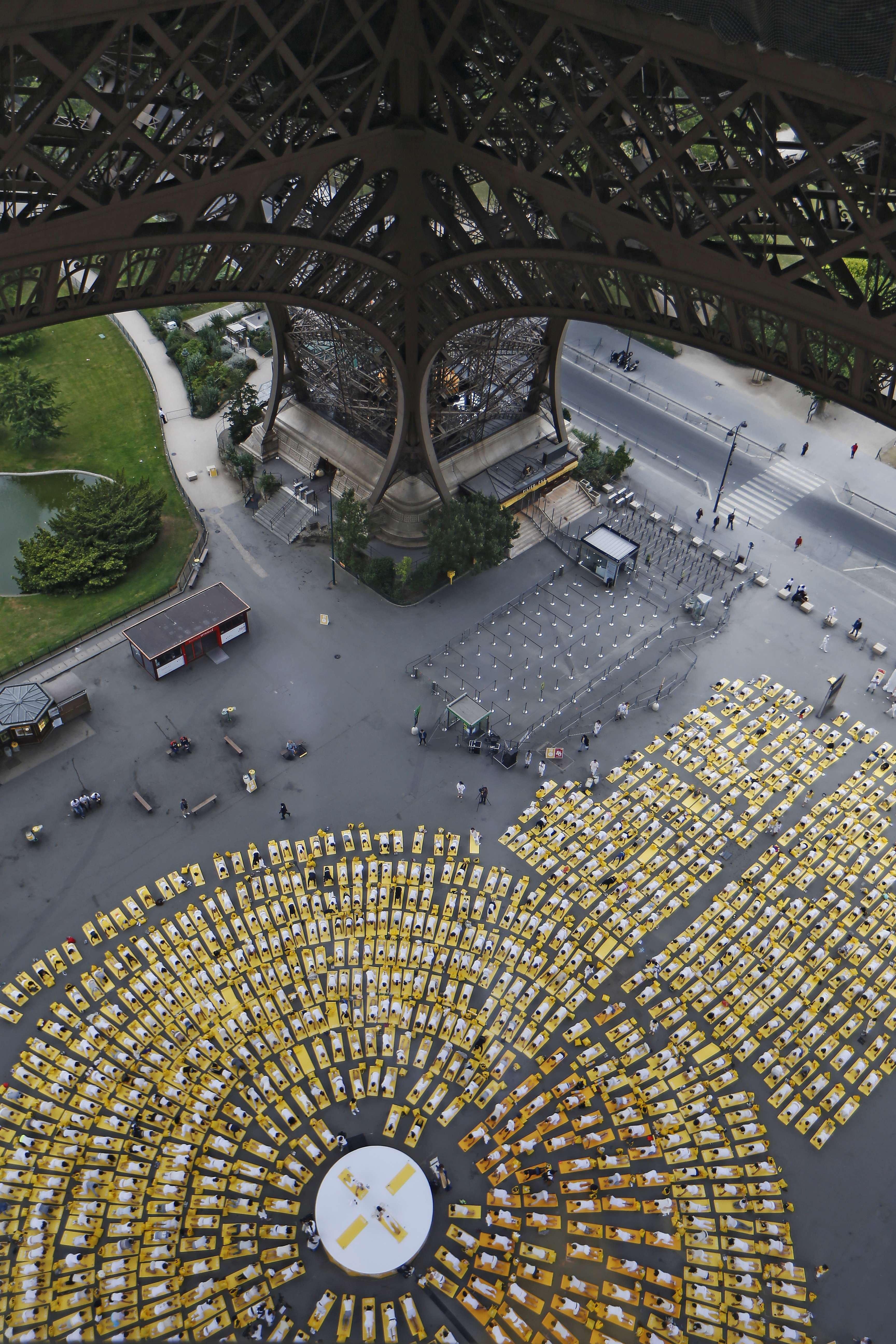 Hundreds of people attend a yoga session under the Eiffel Tower in Paris, on June 21, 2015, in a mass yoga session to mark the first International Yoga Day.