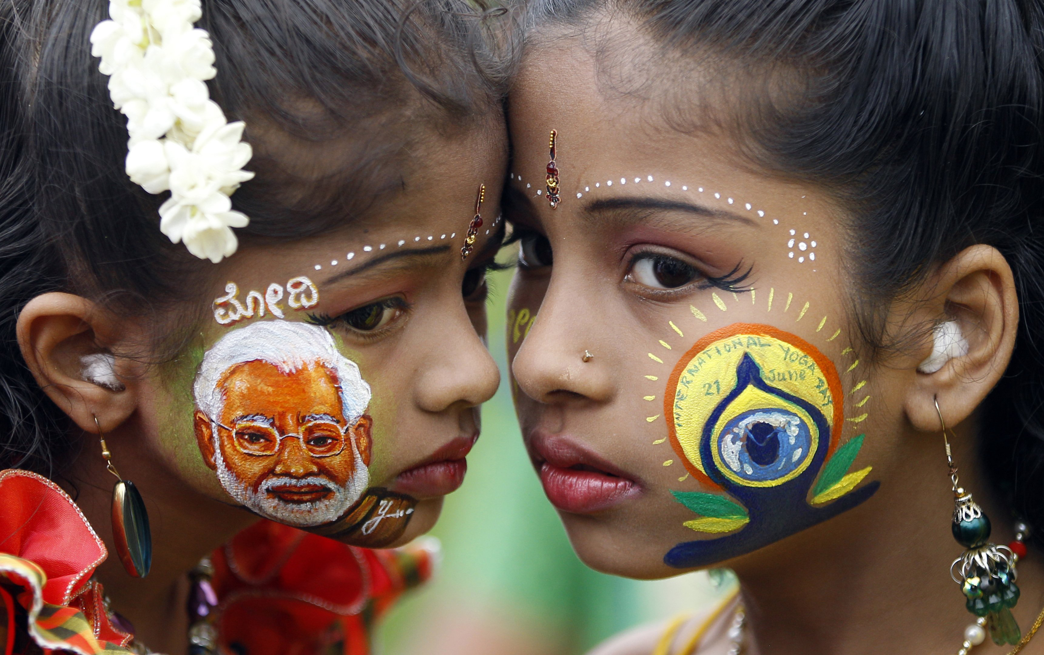 An Indian girl, left, displays a picture of Prime Minister Narendra Modi painted on her face as another sports the logo of International Yoga Day in Bangalore, India, on June 21, 2015.