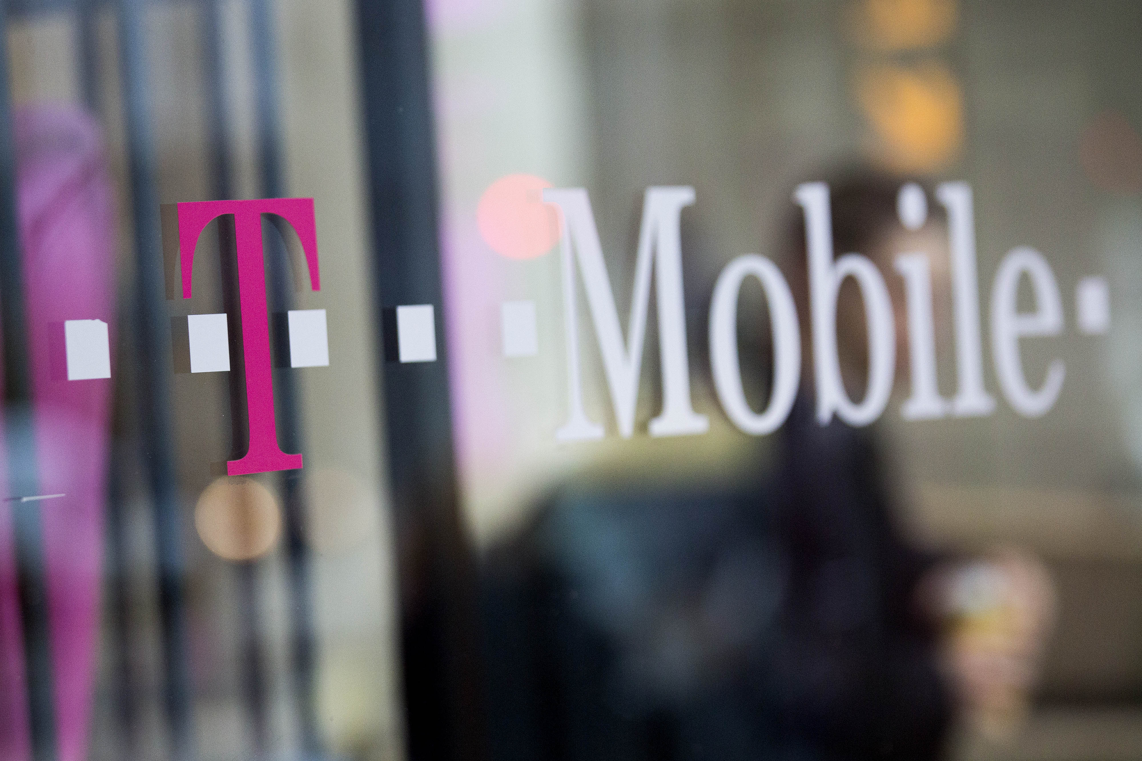 T-Mobile US Inc. signage is displayed in the window of a retail store in Washington, D.C., on Oct. 23, 2014.