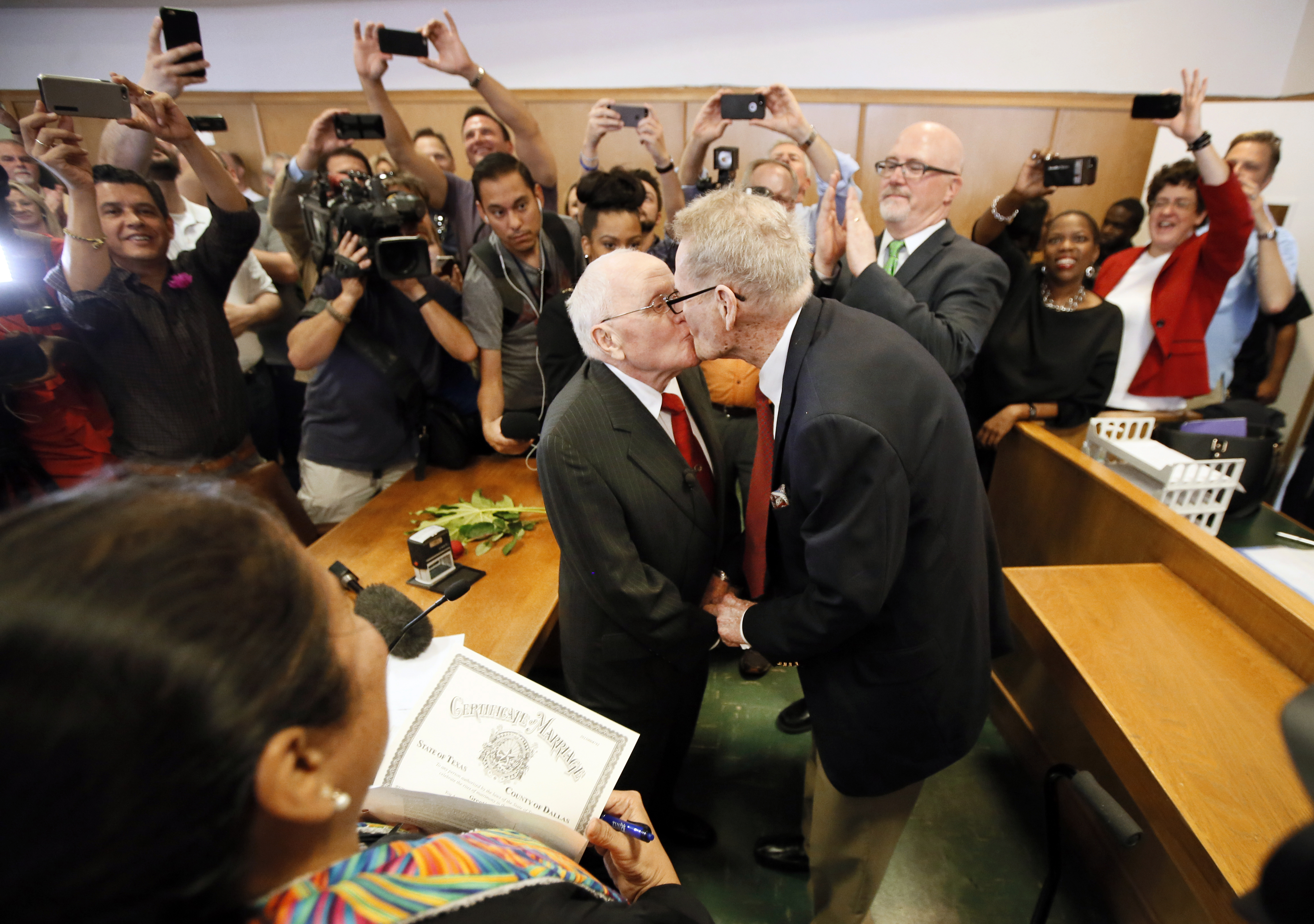 Judge Dennise Garcia, left front, watches as George Harris, center left, 82, and Jack Evans, center right, 85, kiss after being married by Judge Garcia in Dallas on June 26, 2015.