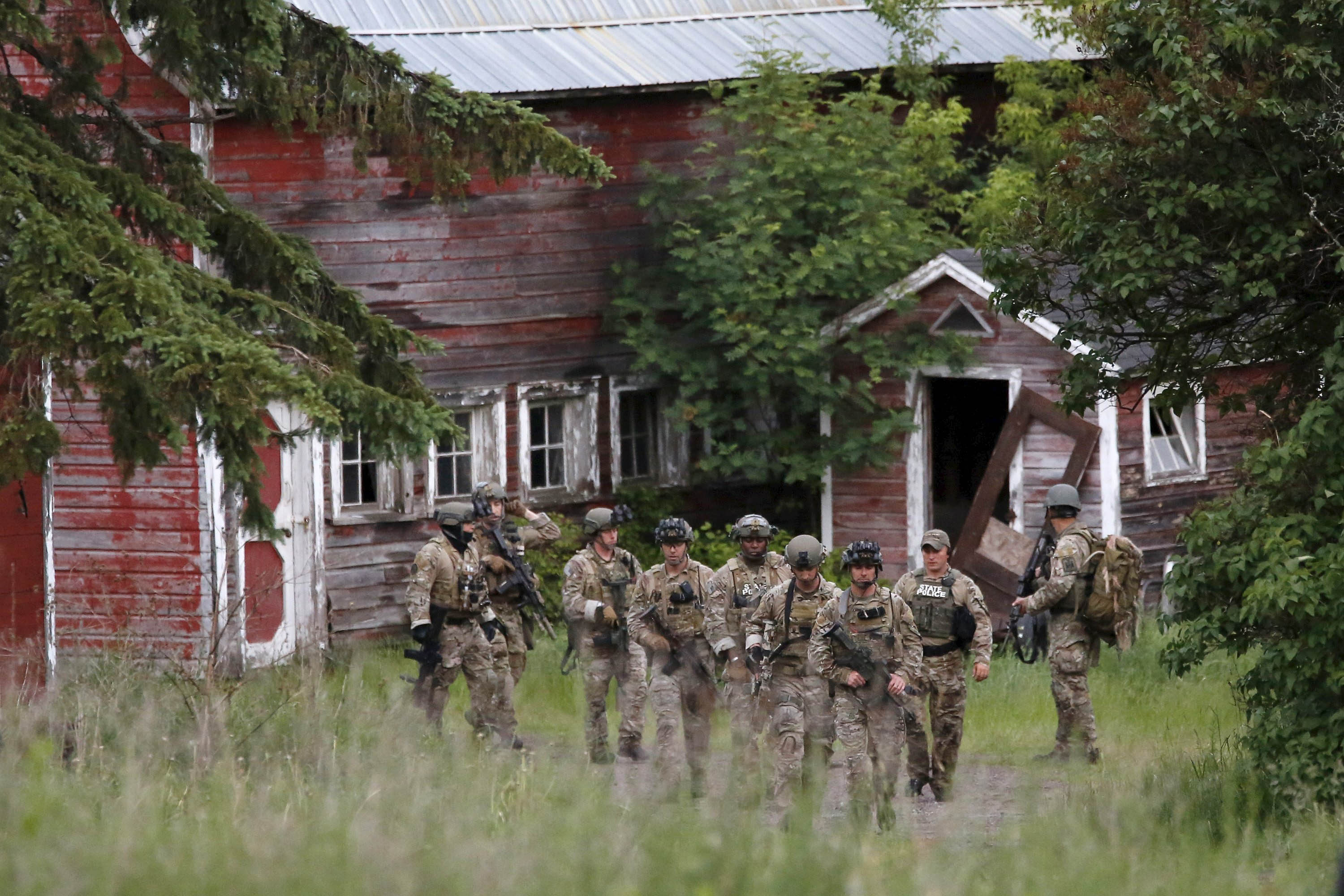 Police dressed in fatigues search near the Clinton Correctional Facility in Dannemora on June 8.