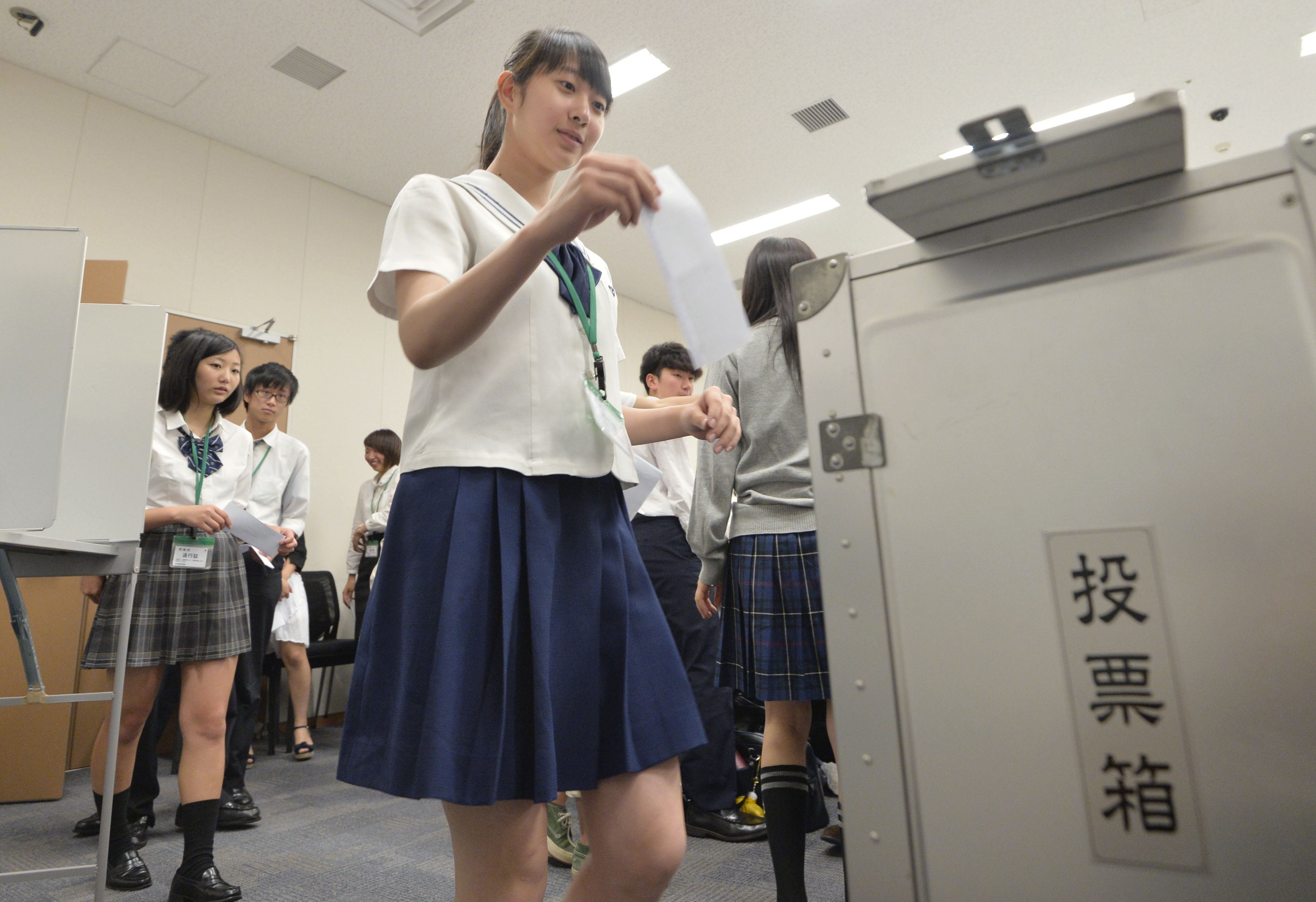 High school students cast their votes for a simulated national election at the parliament building in Tokyo on June 17, 2015.