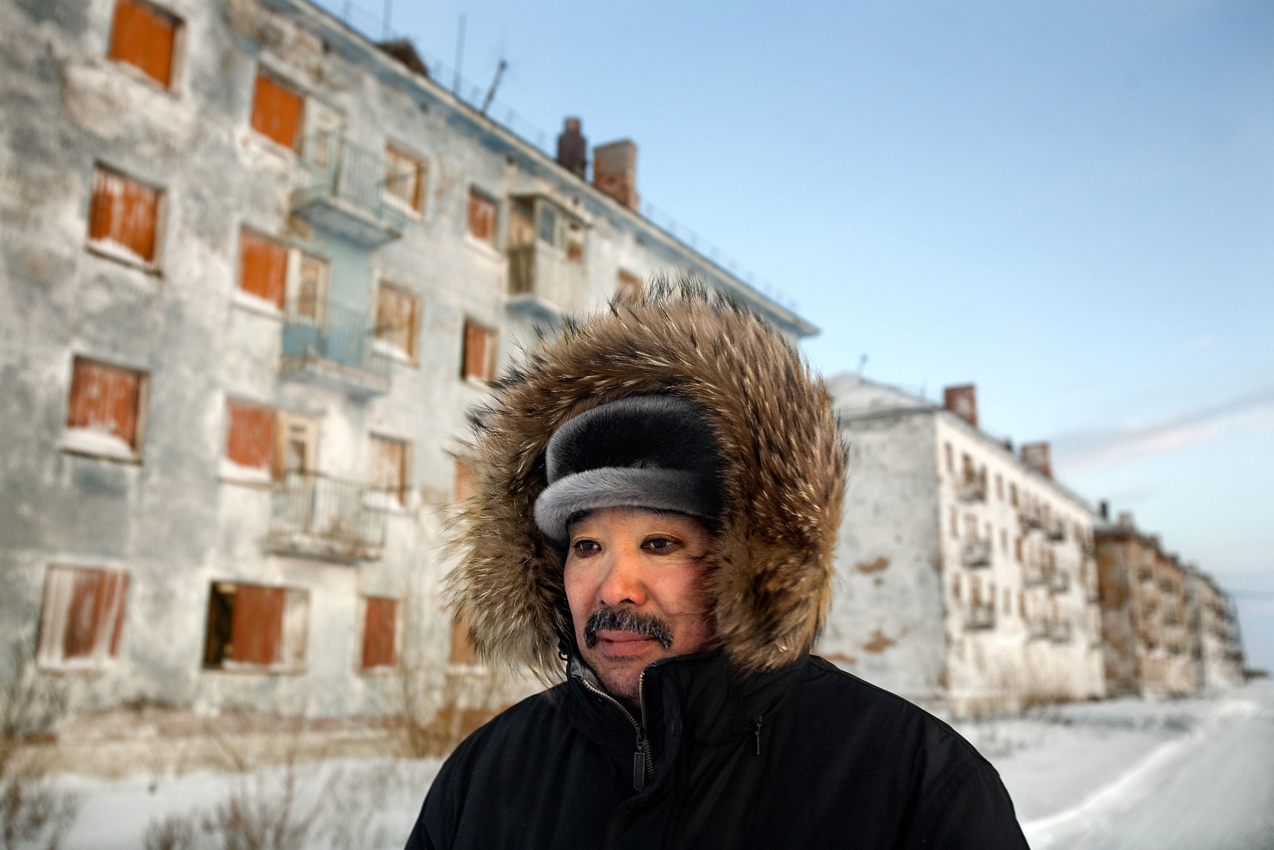 Karp Belgayev, a coal miner, walks through Yorshor, an abandoned village near Vorkuta where he is among the last ten inhabitants. Miners say that after ten years working underground and poor washing, it is impossible to remove black rings from around the eyes, January 2009.