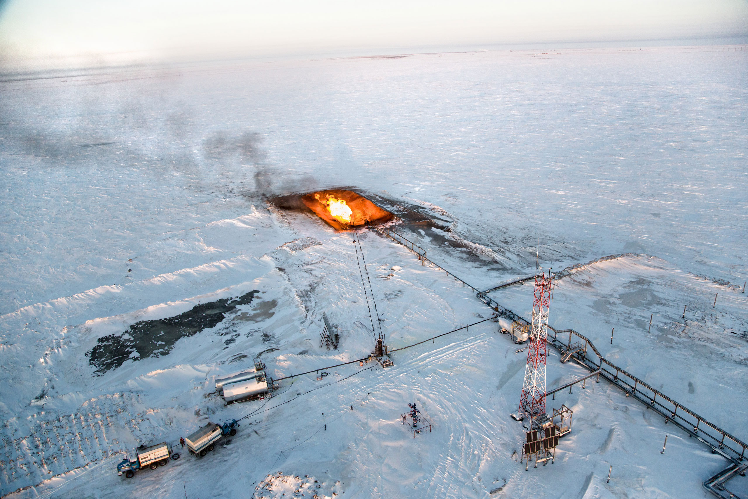A gas flare is seen overhead at a drilling well in Novy Urengoi, Arctic Siberia, Russia, December 2014.