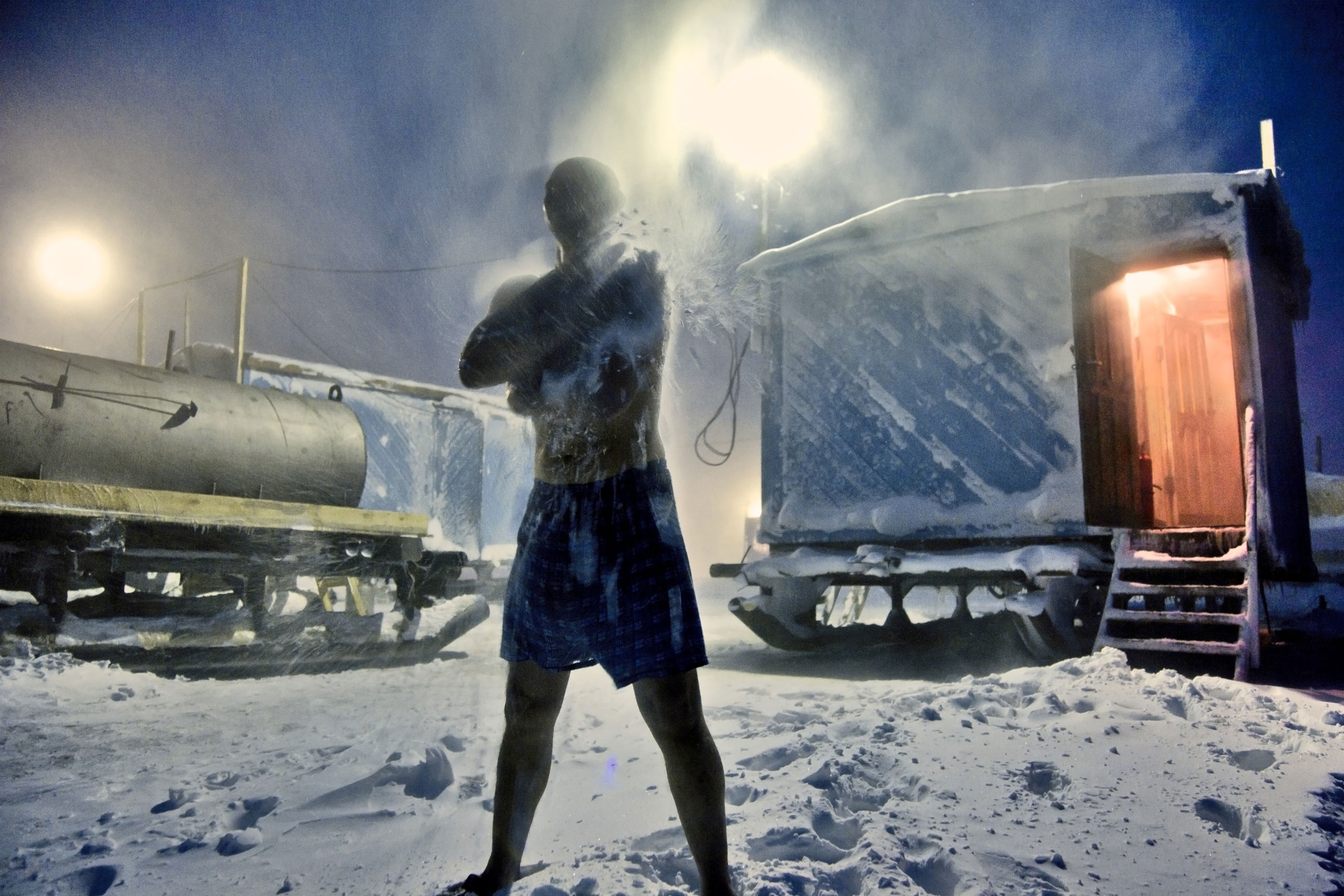 A Russian oil worker rubs himself with snow outside a mobile sauna in the Arctic tundra. The water is heated by a diesel tank, February 2012.