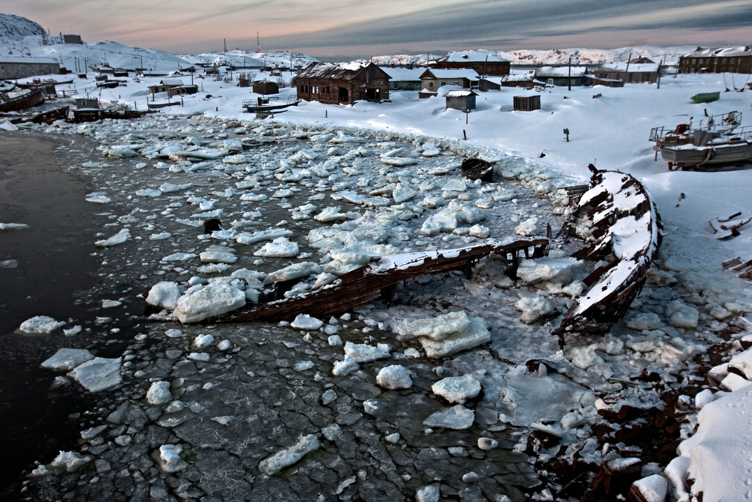 Sunken boats and abandoned houses lay rotting by an icy bay in Teriberka, a former prosperous fish-processing community waiting for an economic boom through gas production, February 2012.