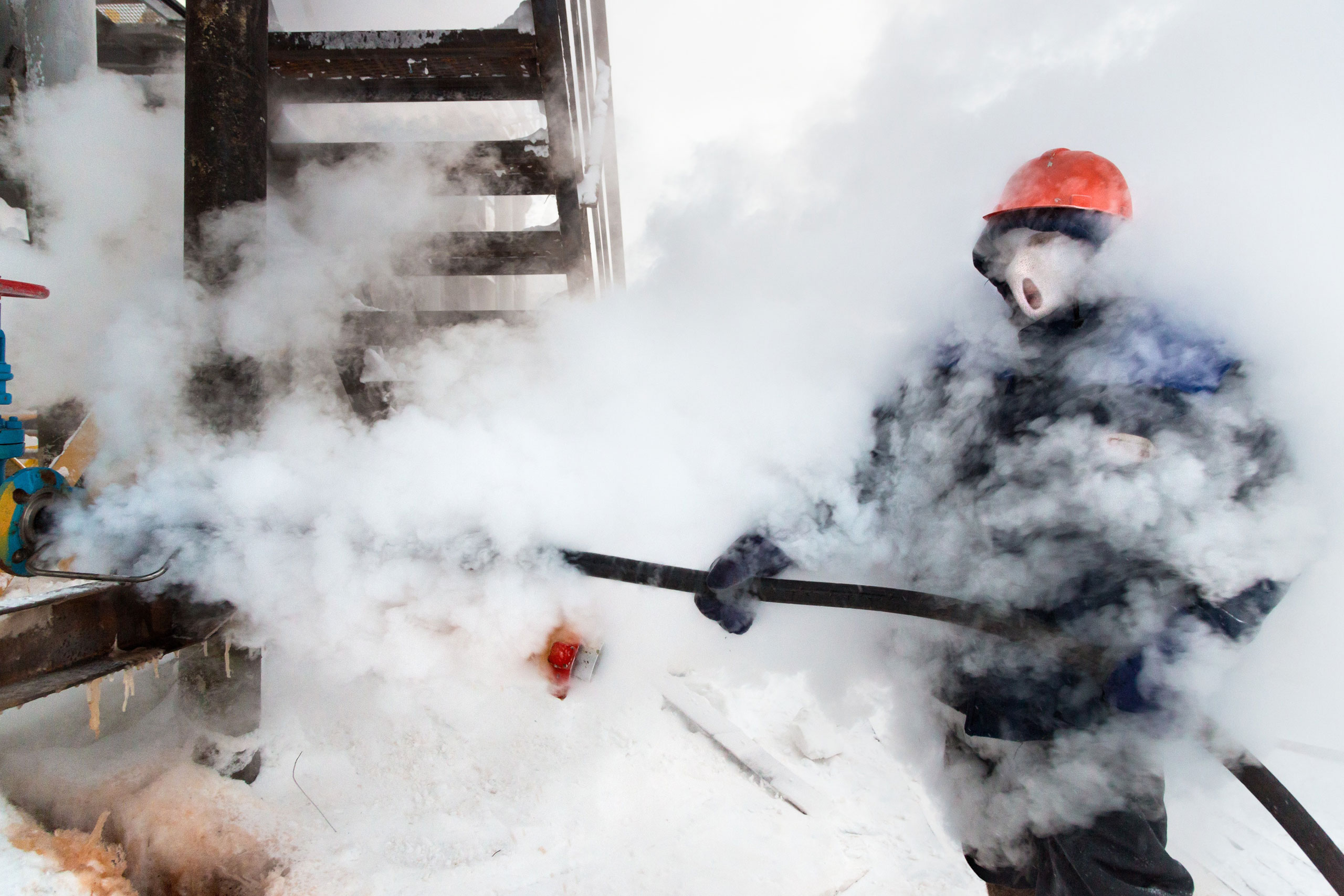 A Russian gas worker sprays steam to unfreeze pipes in Novy Urengoi, Arctic Siberia, Russia, December 2014.