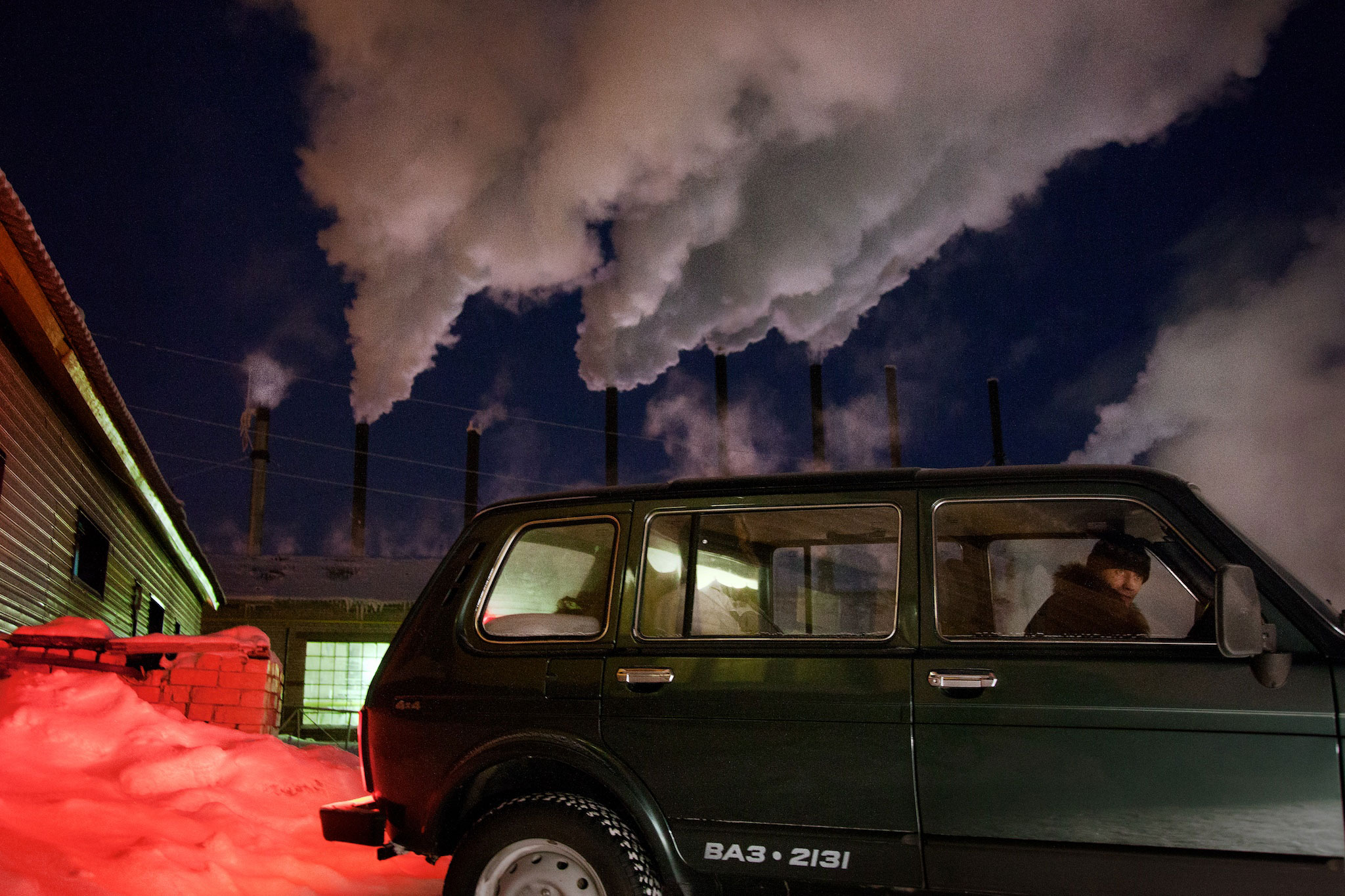 A car drives past a water-heating plant in Naryan-Mar, capital of the resource-rich Nenets Autonomous Region in Arctic Russia, where many of the oil and gas exploration companies have their local headquarters, February 2011.