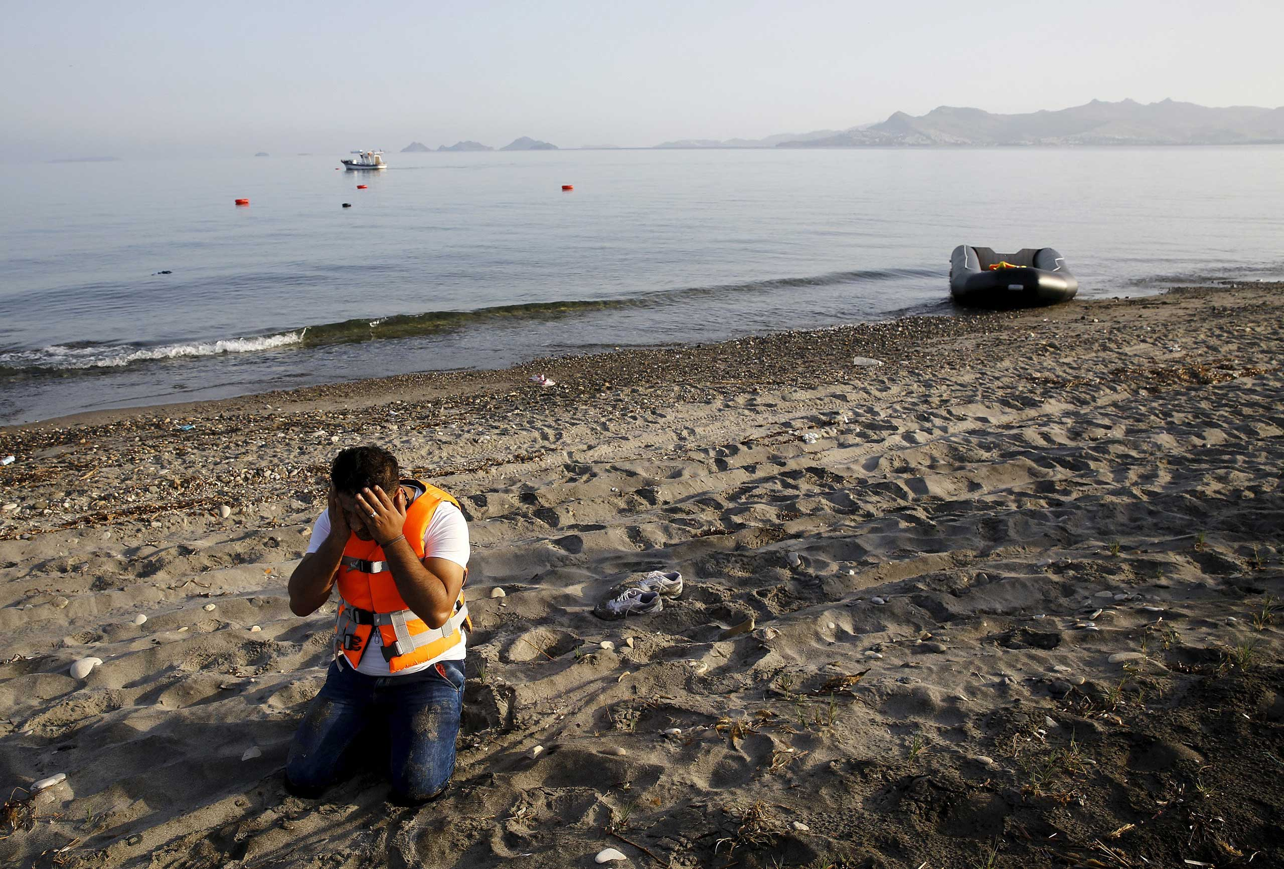 A Syrian refugee prays on the beach after arriving on the Greek island of Kos, via a dinghy boat over part of the Aegean Sea from Turkey to Greece, on May 26, 2015.