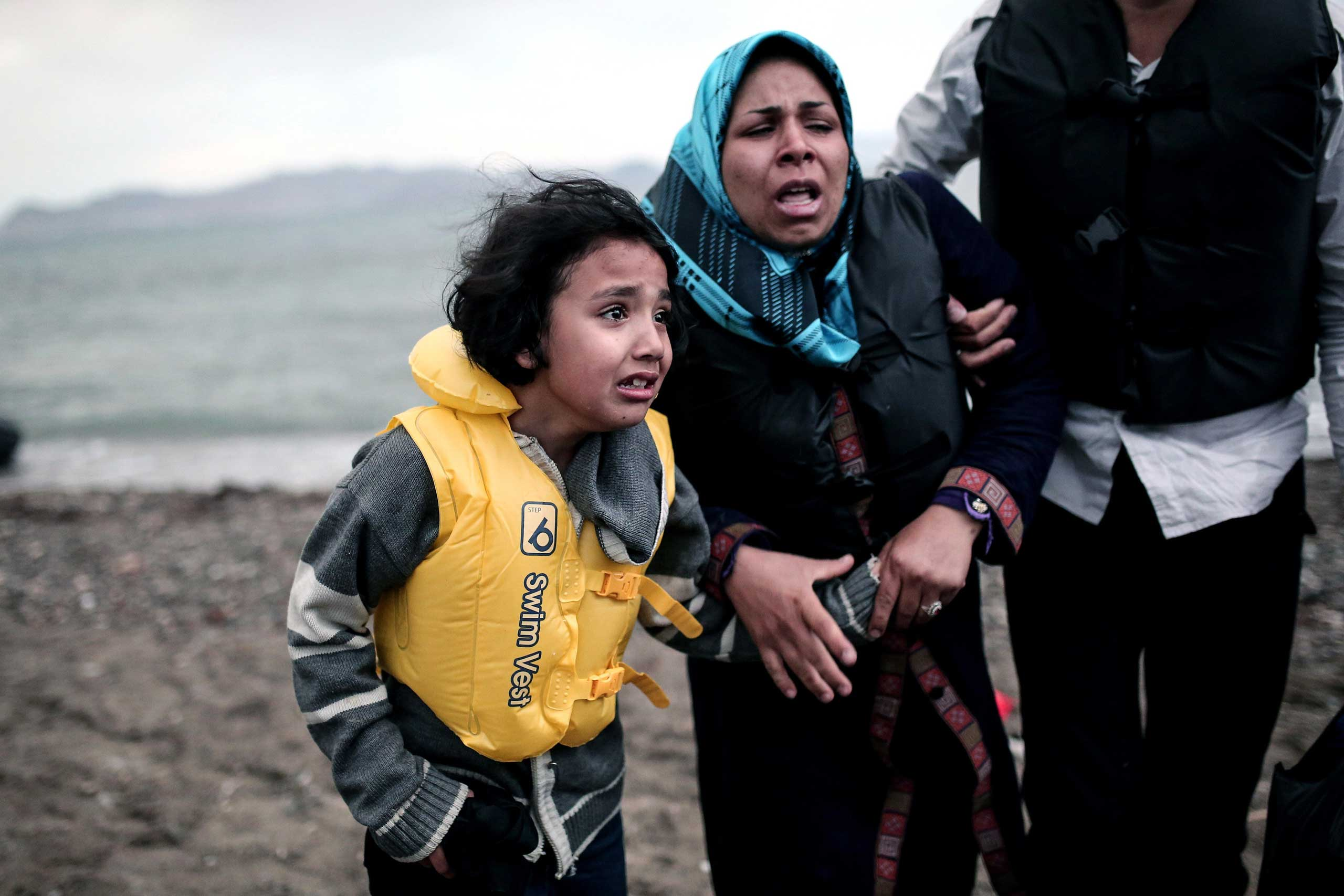 An Afghan migrant girl holds the hand of a woman as they arrive on the Greek island of Kos, after crossing a part of the Aegean Sea between Turkey and Greece, on May 27, 2015.