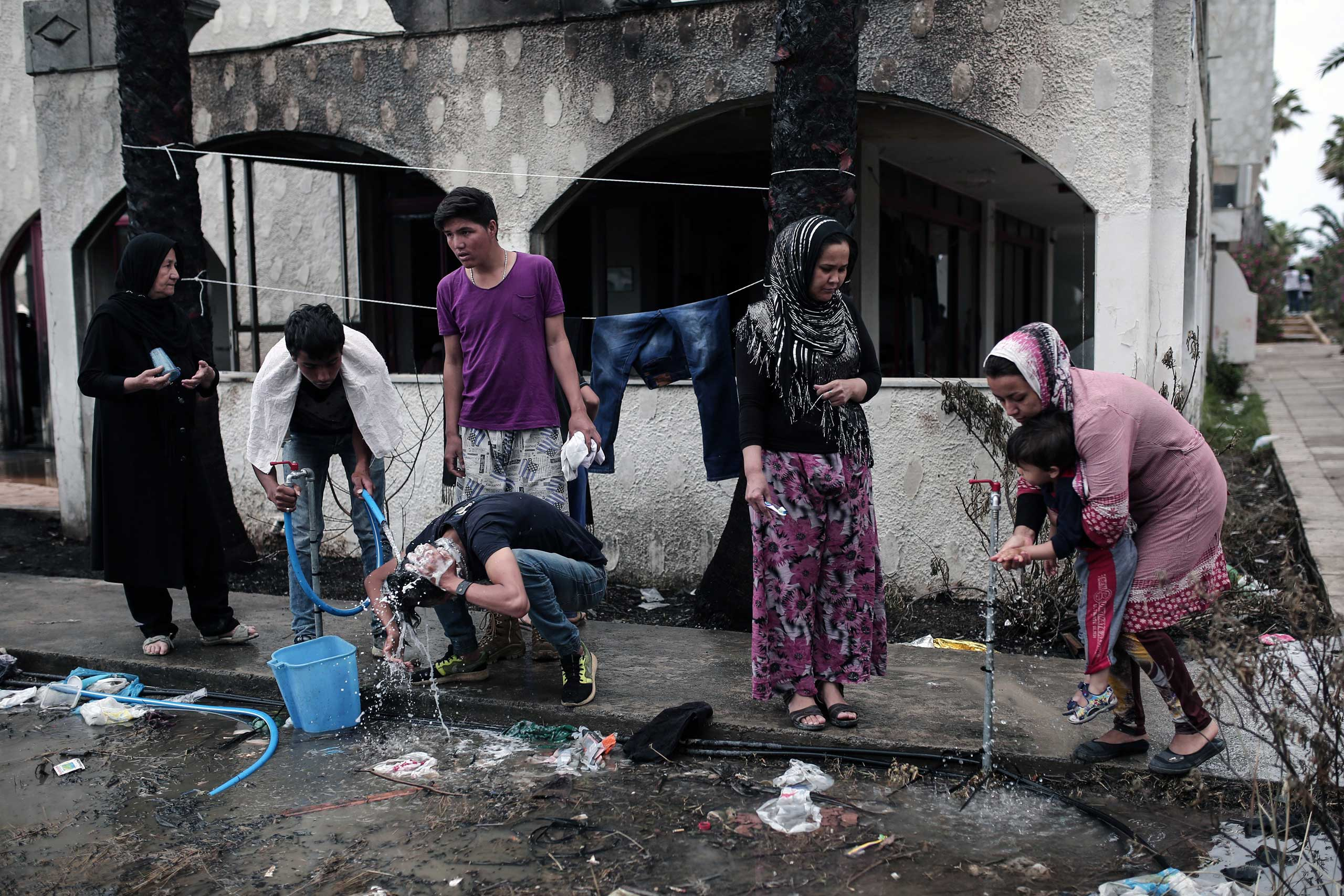 Afghan migrants wash next to a deserted hotel, where hundreds of migrants have found temporary shelter, on the Greek island of Kos on May 27, 2015.