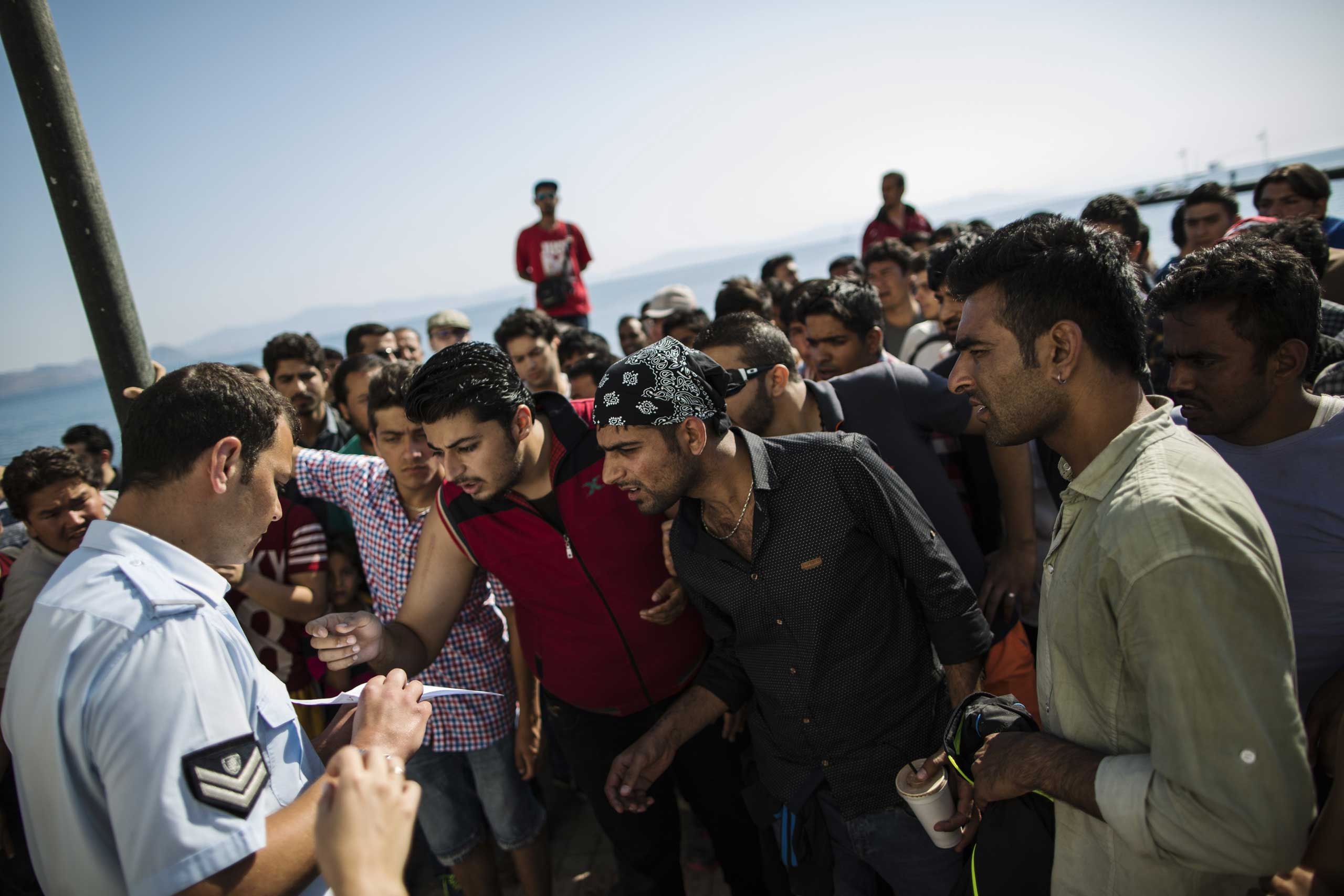 Migrants gather outside the police station on the Greek island of Kos to collect documentation to facilitate their onward journey into Europe on June 1, 2015.