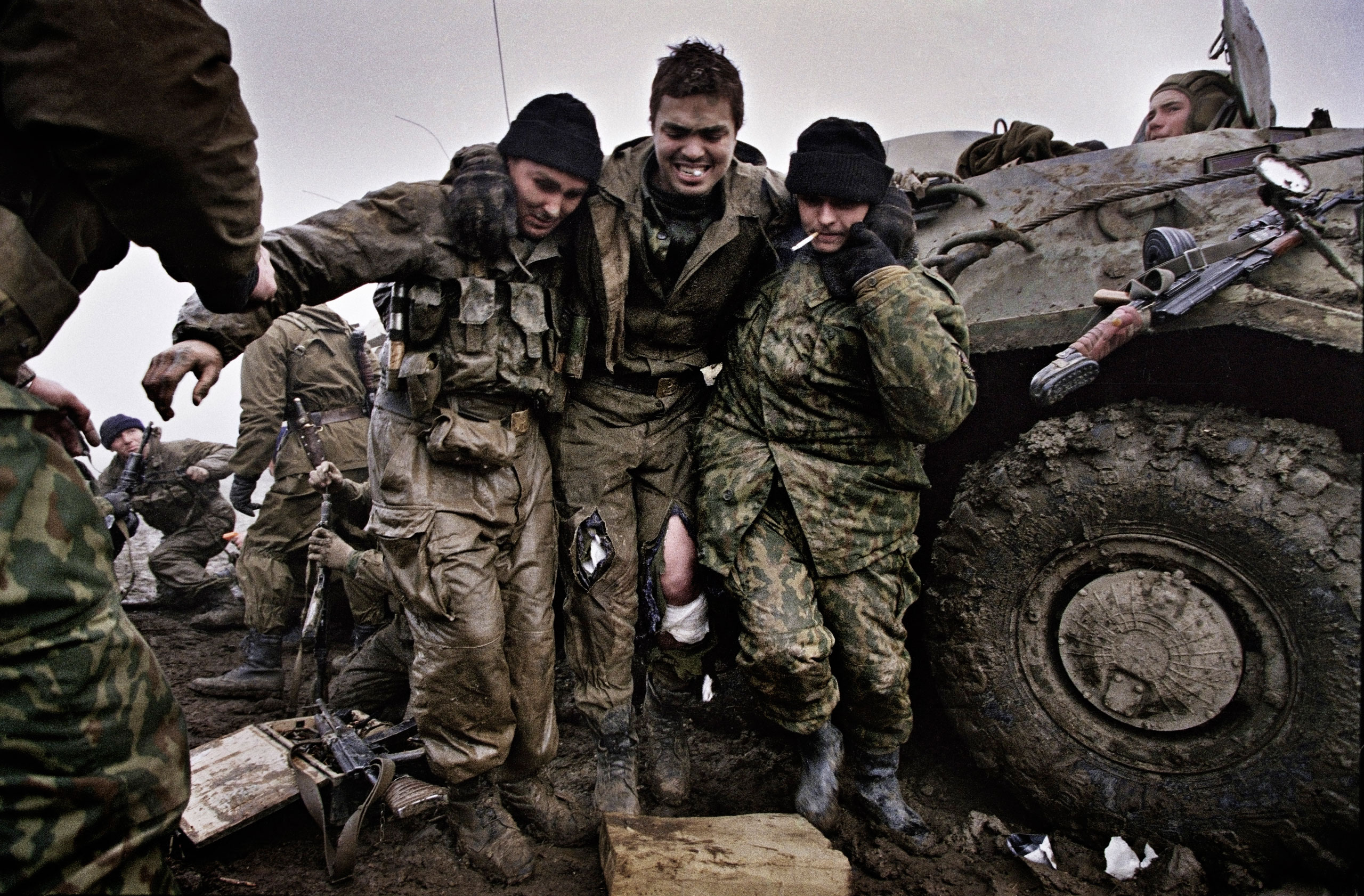 Russian marines help a wounded fellow soldier after being caught in an ambush near Tsentaroy, Chechnya, December 1999.