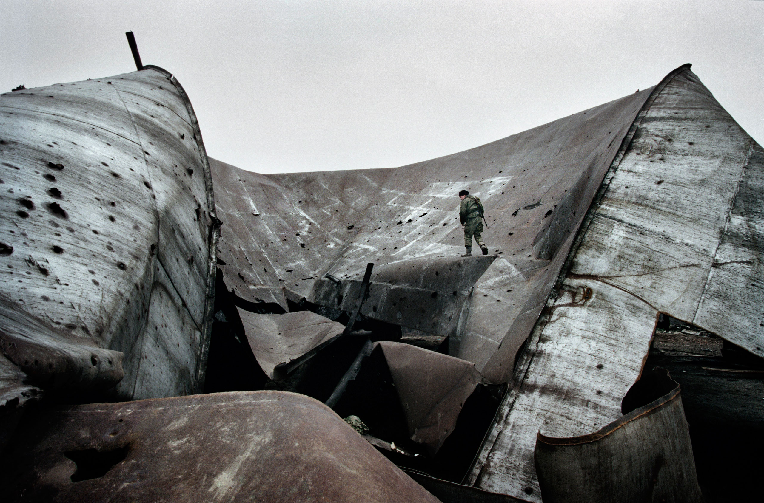 A  russian soldier at an  oil refinery storage facility that was destroyed in the first Chechen War, Tsentaroy, Chechnya, December 1999. Chechnya's plentiful crude oil is one of  the main reasons why Russia refused to allow the region to secede.