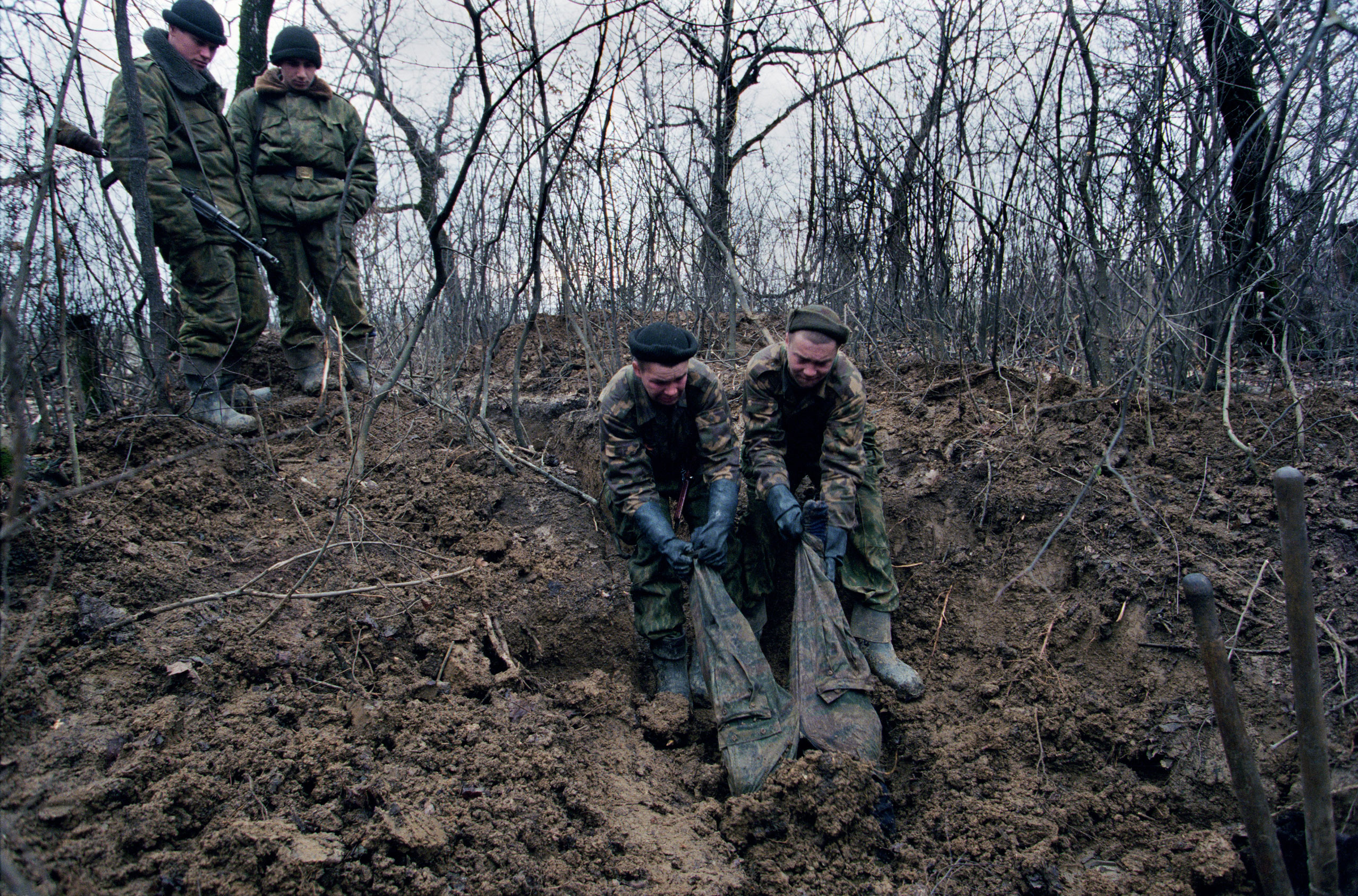 Russian forces uncover  the body of  a dead rebel in Tsentaroy, Chechnya, the native village of the Kadyrov clan, December 1999.