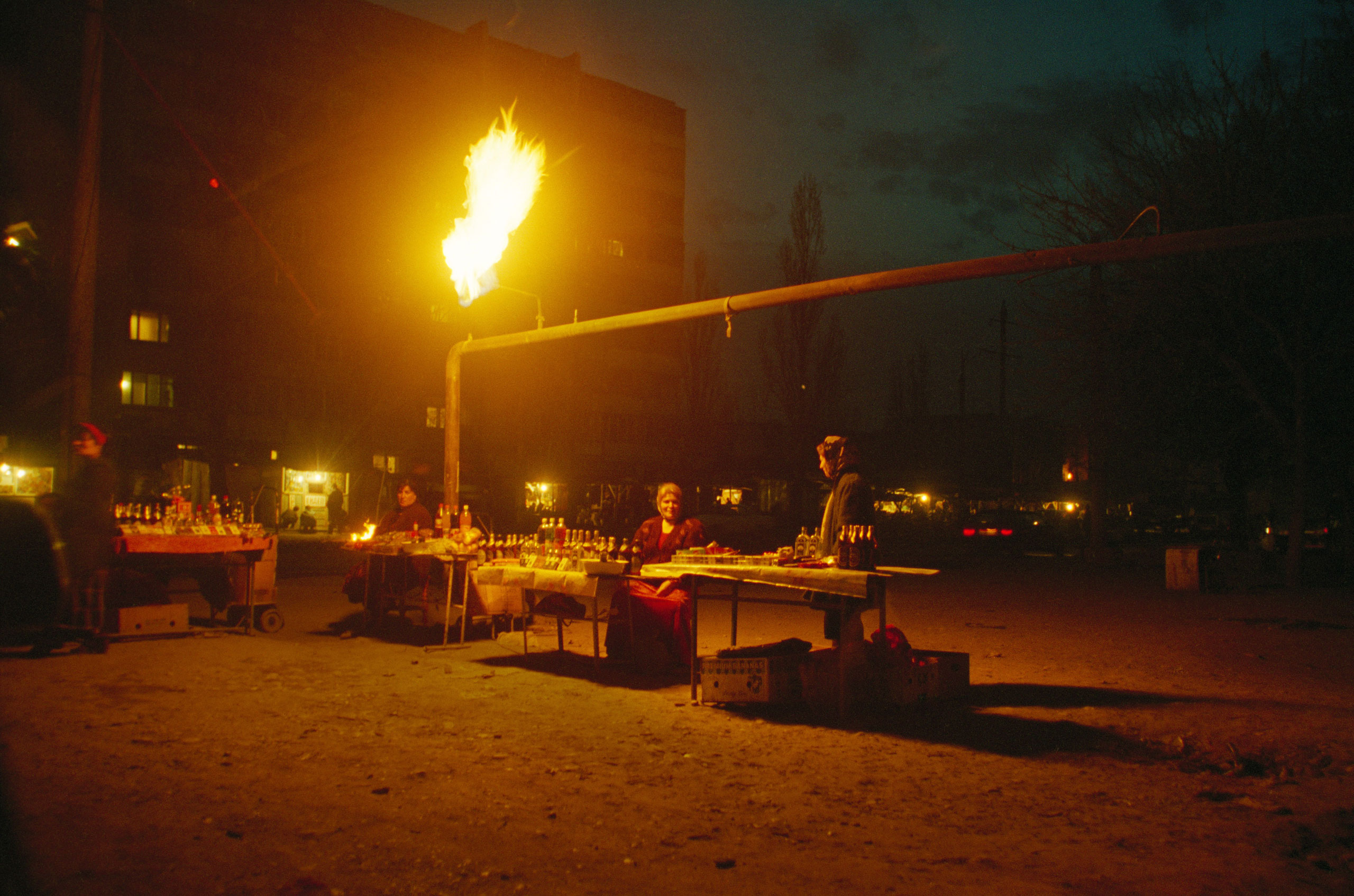 Women sell their wares while a gas pipeline burns in Grozny, Chechnya, February, 2002.