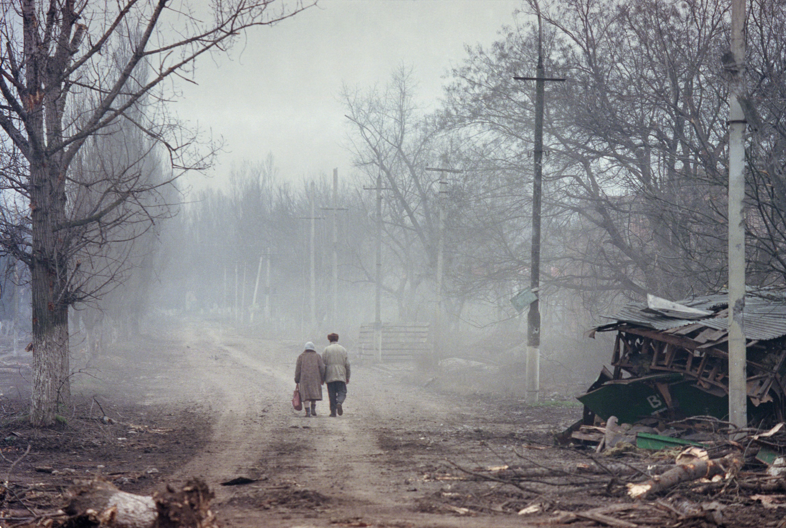 A couple walks through  the ruins of Grozny, the capital of Chechnya, which was flattened by Russian air strikes in the second Chechen war, March 2002.