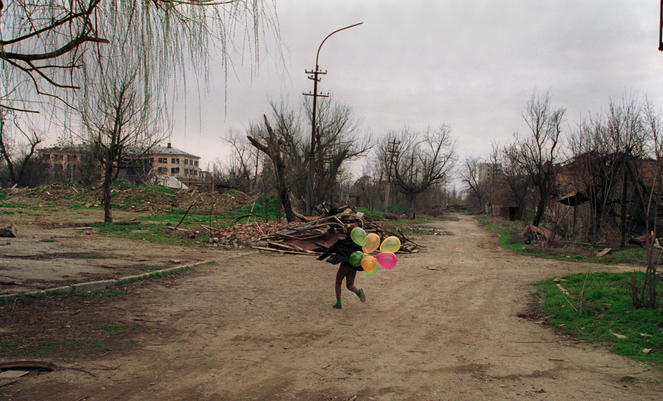 A child with balloons plays in downtown Grozny, Chechnya, March 2002.