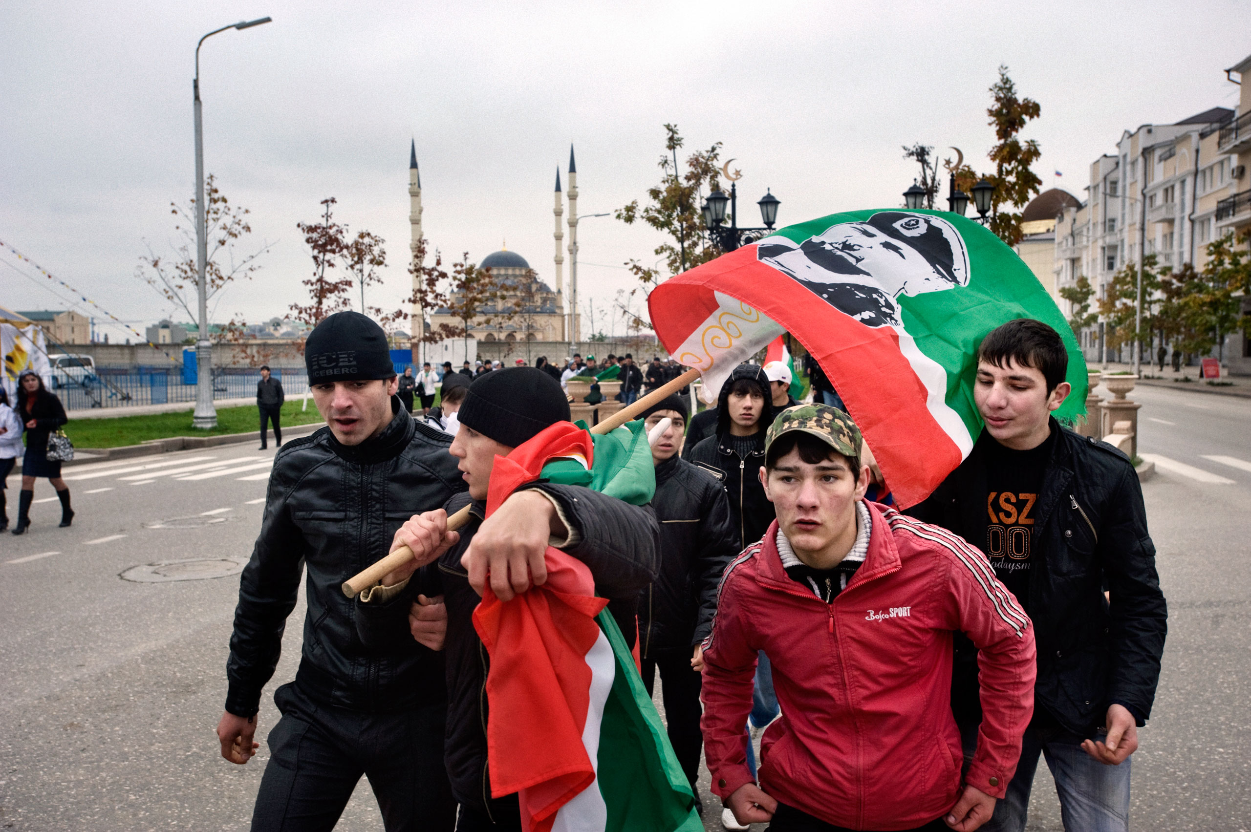 Members of the patriotic club Ramzan hold flags picturing Chechen leader Kadyrov on Putin's avenue, Grozny, Chechnya, November 2009.