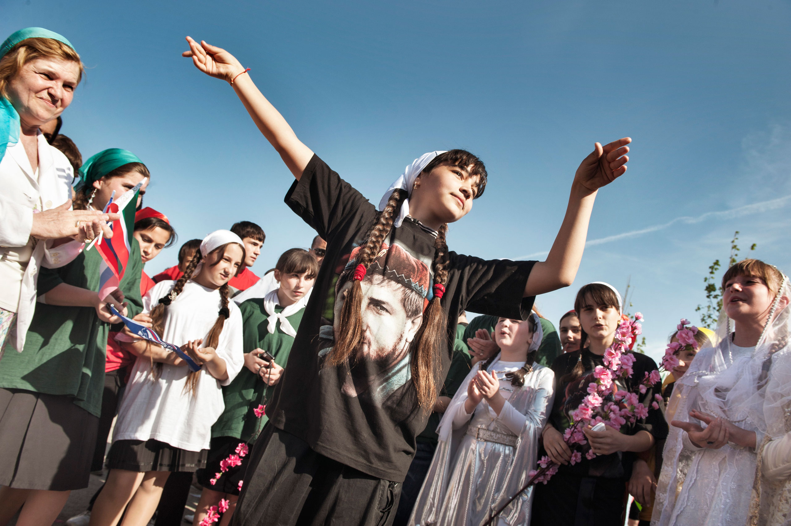 A Chechen girl dances while wearing a shirt showing a portrait of Ramzan Kadyrov, the Kremlin-backed leader of Chechnya, in the town of Gudermes, Chechnya, May 2010.