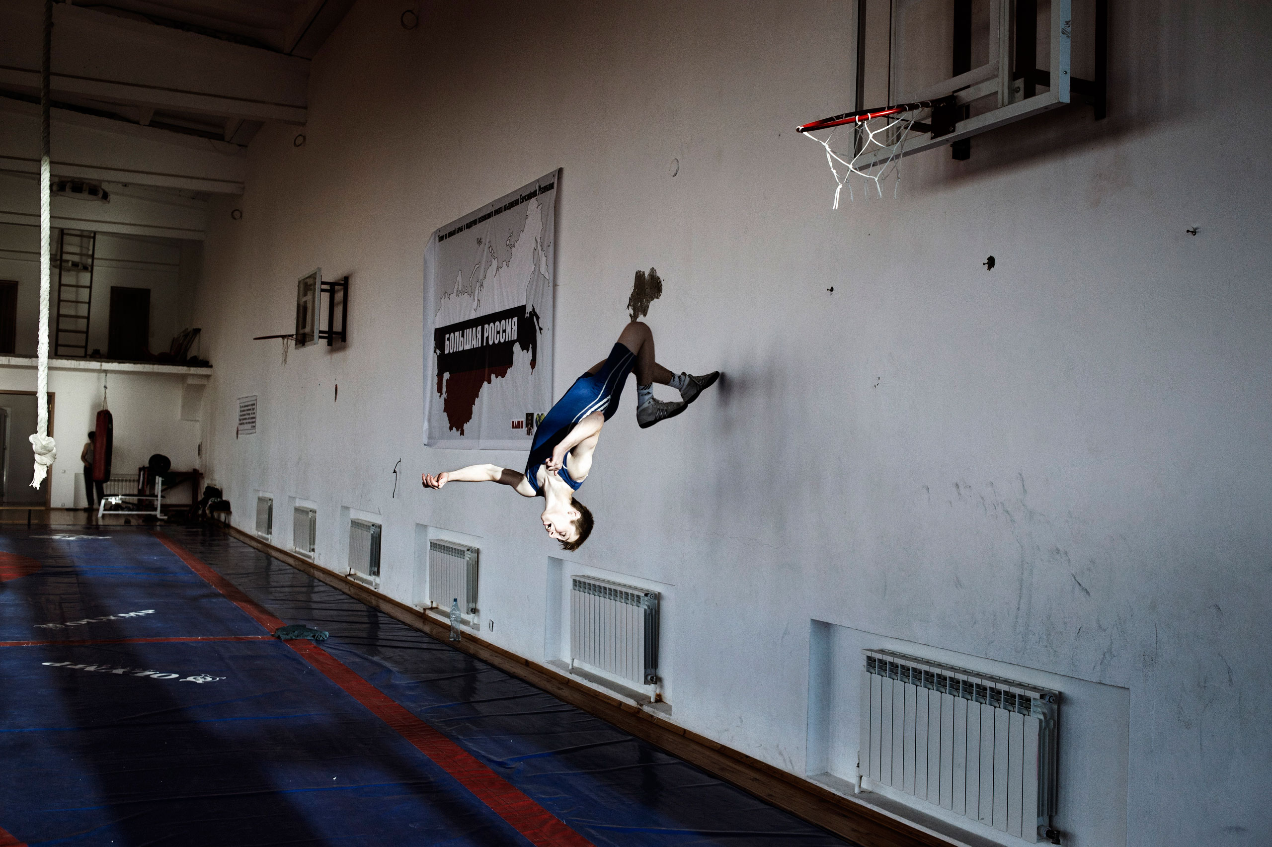 An amateur wrestler does a backflip against the wall of his gym during training in Khasav-Yurt, in the neighboring Dagestan. Moscow financially supports Khasavyurt's wrestling academies, which offer an outlet for local youth to channel their strength to wrestling rather than rebellion, June 2012.