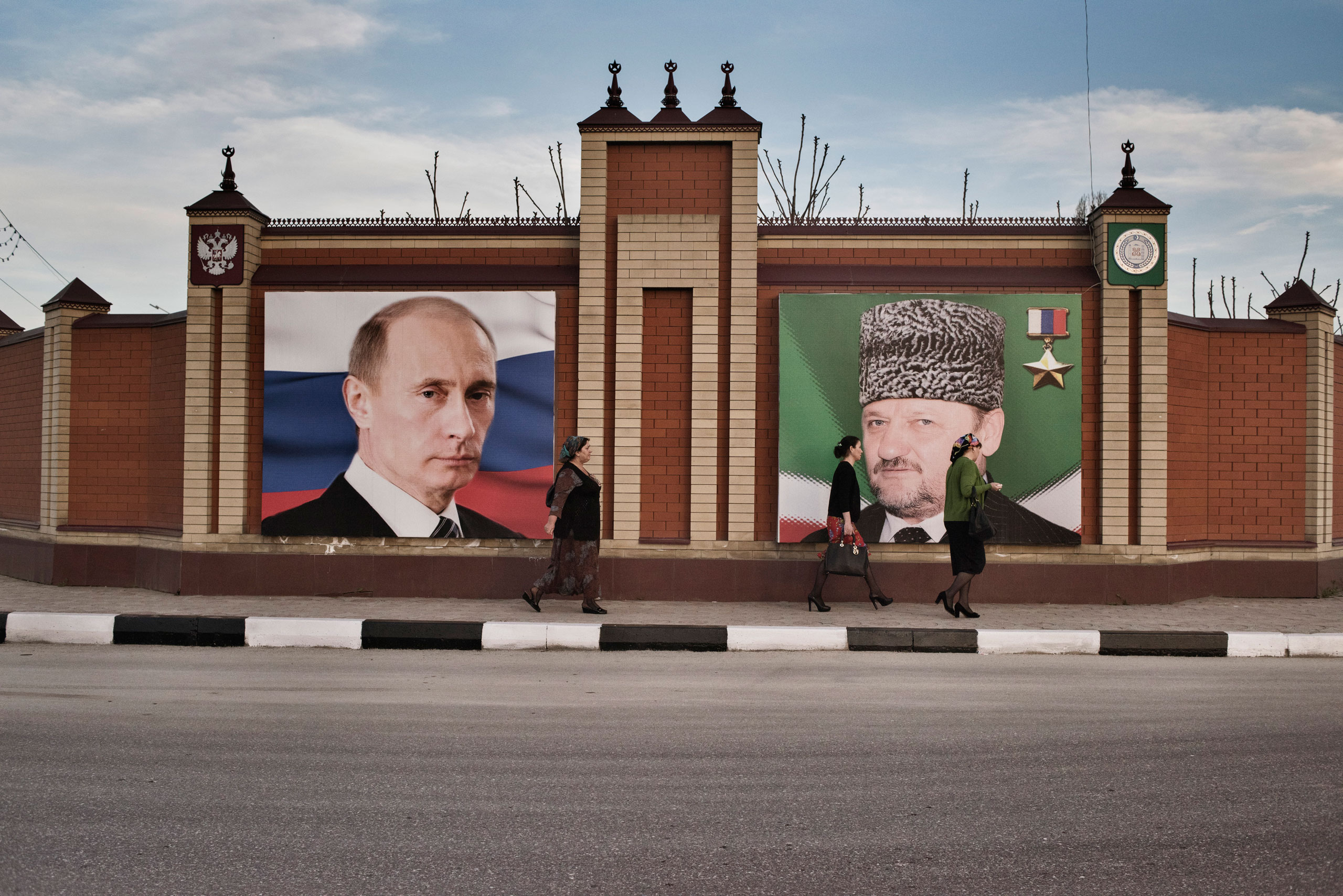 Women walk past a portrait of Russian President Vladimir Putin and the late President of Chechnya, Akhmad Kadyrov, the father of Chechnya's current leader, Ramzan Kadyrov, Throughout the region, portraits of Putin and the Kadyrovs are plastered on the facades of buildings and along highways, Grozny, Chechnya, April 2015.