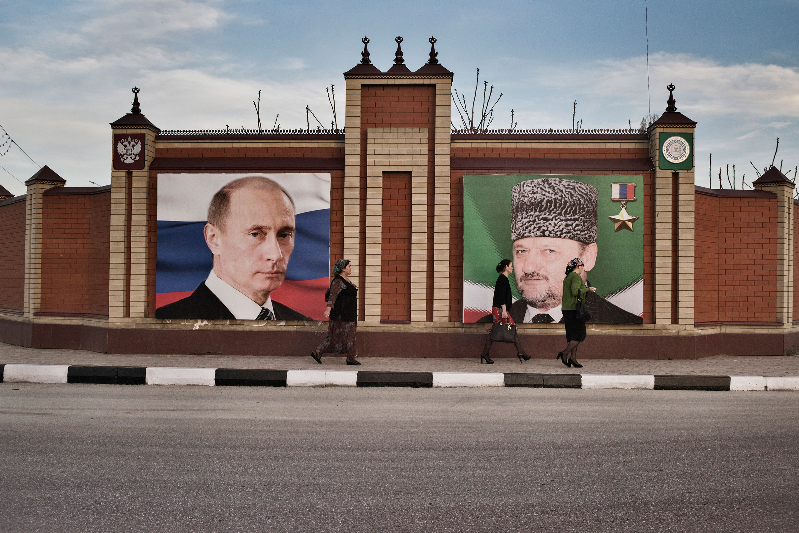 Women walk past a portrait of Russian President Vladimir Putin and the late President of Chechnya, Akhmad Kadyrov, the father of Chechnya's current leader, Ramzan Kadyrov, Throughout the region, portraits of Putin and the Kadyrovs are plastered on the facades of buildings and along highways, Grozny, Chechnya, April 2015.From  Yuri Kozyrev: Photographing 15 Years of Chechnya's Troubled History