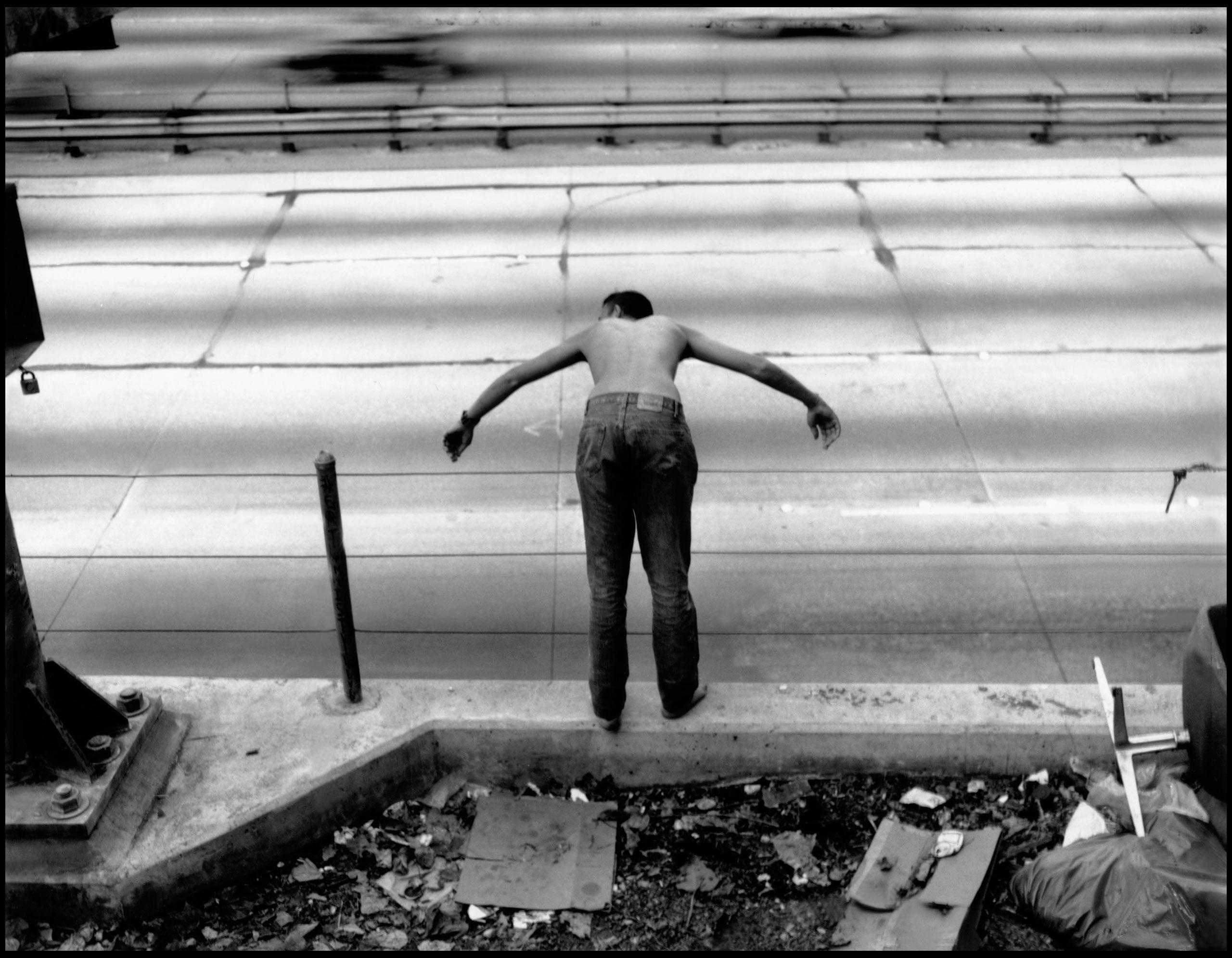 """Untitled, 1995.""""This photograph is part of a larger project called Raised by Wolves, which was a ten-year multimedia project photographing homeless street kids in San Francisco and Hollywood.                               [The man] was playing chicken, which is how far he could lean over the railing of the freeway before he would fall off. Right behind him was an area underneath a freeway overpass where a bunch of kids were sleeping""""—Jim Goldberg"""