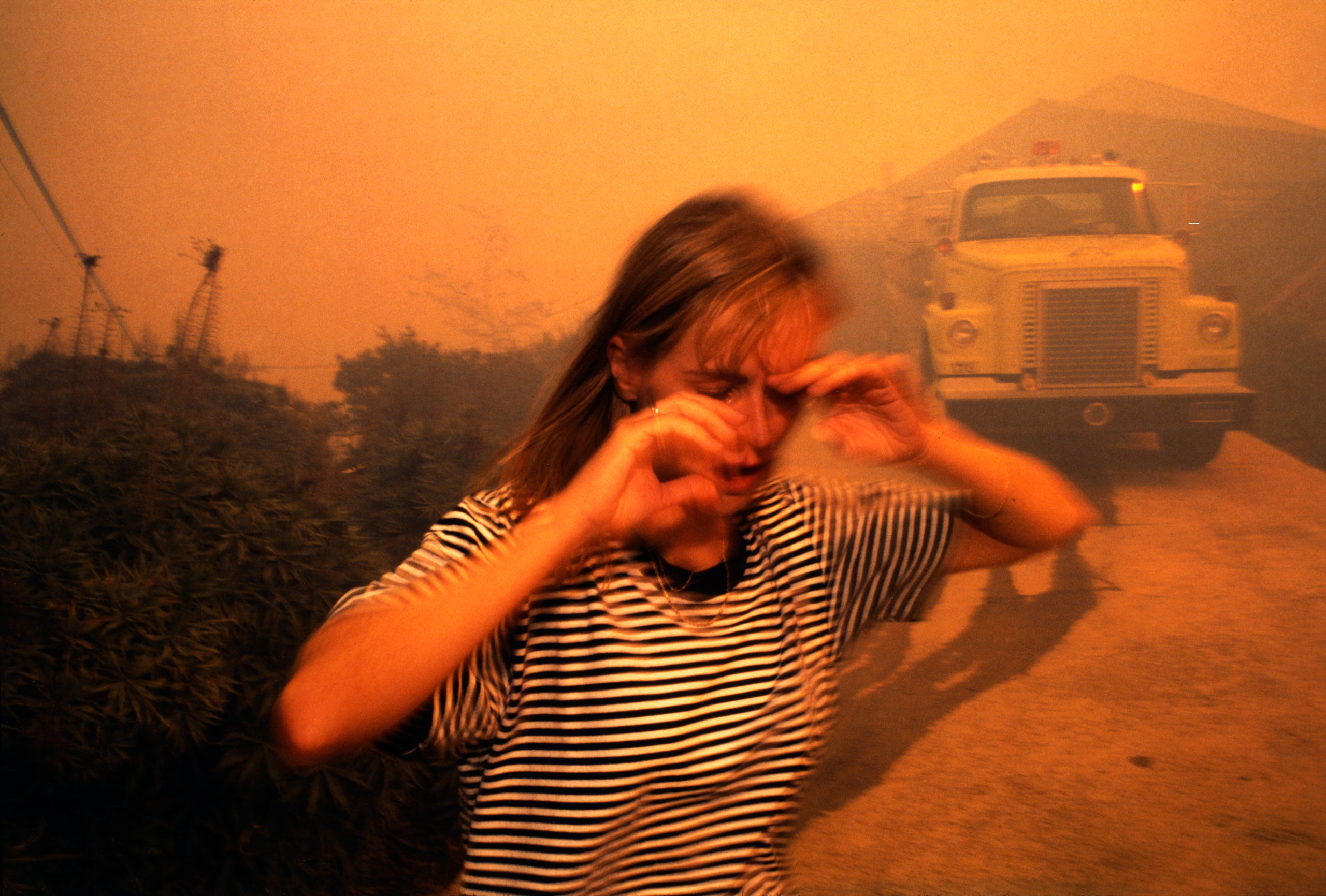 Girl Running from Malibu Fires, 1993.                                 I was not supposed to be in the spot I took this picture. The 1993 Malibu firestorm was so fierce, even credentialed journalists were not allowed up into the hills to cover the epic blaze.                               I had just been disgorged from a first aid truck I had snuck a ride to the scene with when I spotted the girl in the picture, bursting out of a swanky but imminently threatened hilltop home and running right past me into a blood orange hazy hue that seemed to belong to the atmosphere of some exoplanet  —Lara Jo Regan