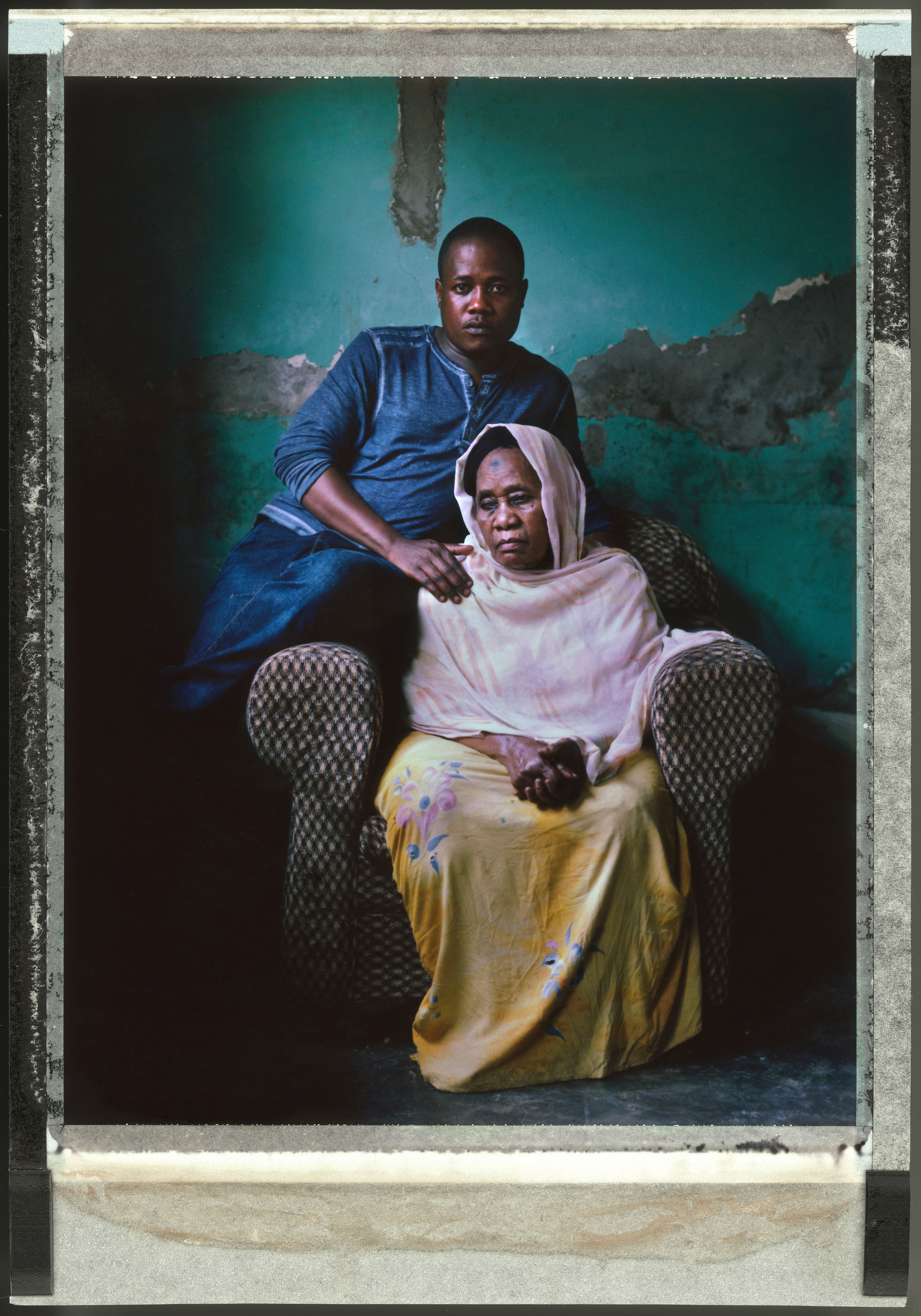 Joseph Kawesi, 31, a transgender woman and gay-rights campaigner, sits with her mother Mai at home in Kampala.