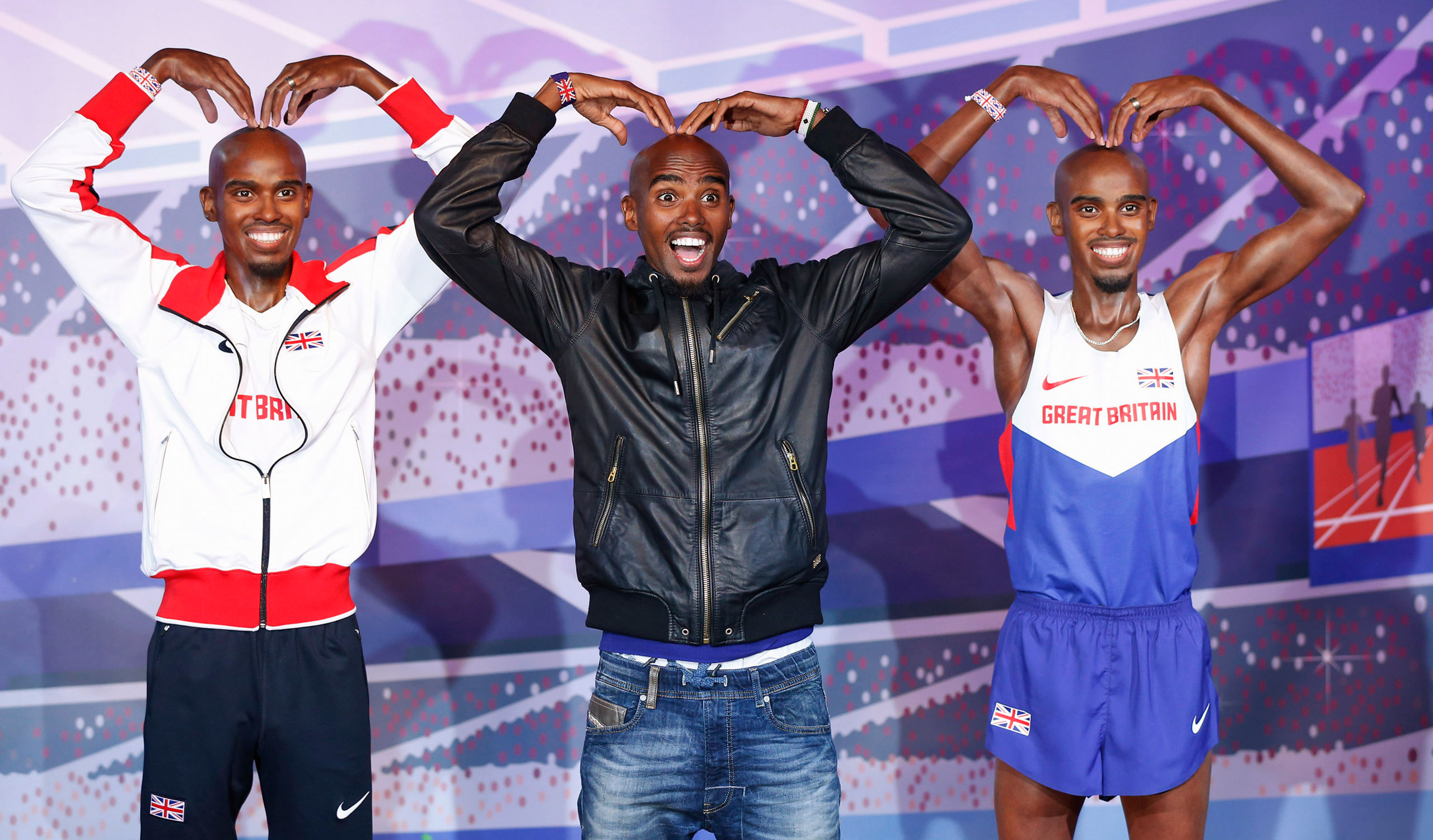 British Olympic athlete Mo Farah, center, poses with two of his waxworks in London on April 14, 2014.