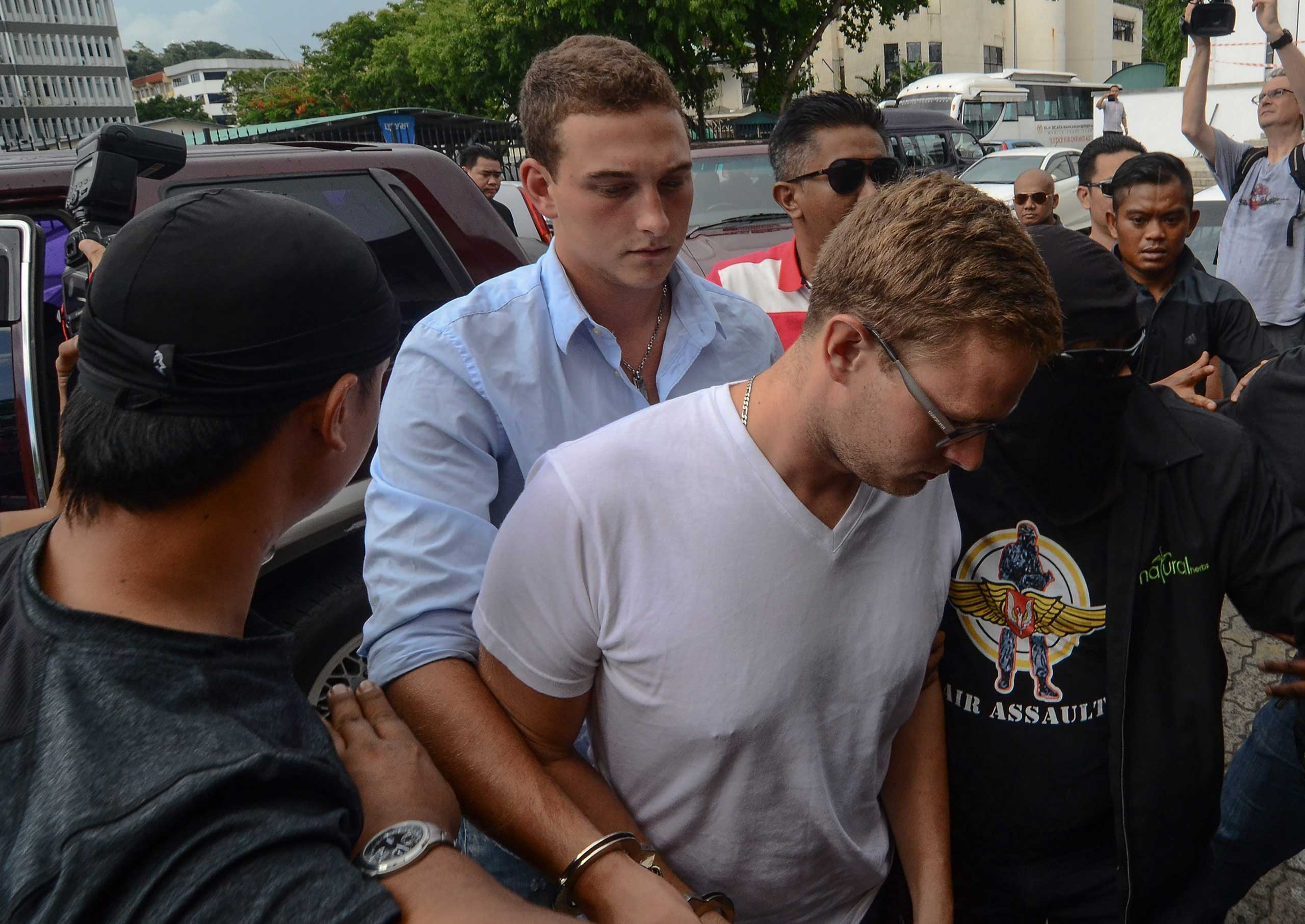 Dutch national Dylan Snel (centre R), 23, and Canadian national Danielle Petersen (centre L), 22, arrive at a court in Kota Kinabalu, Malaysia on June 12, 2015.