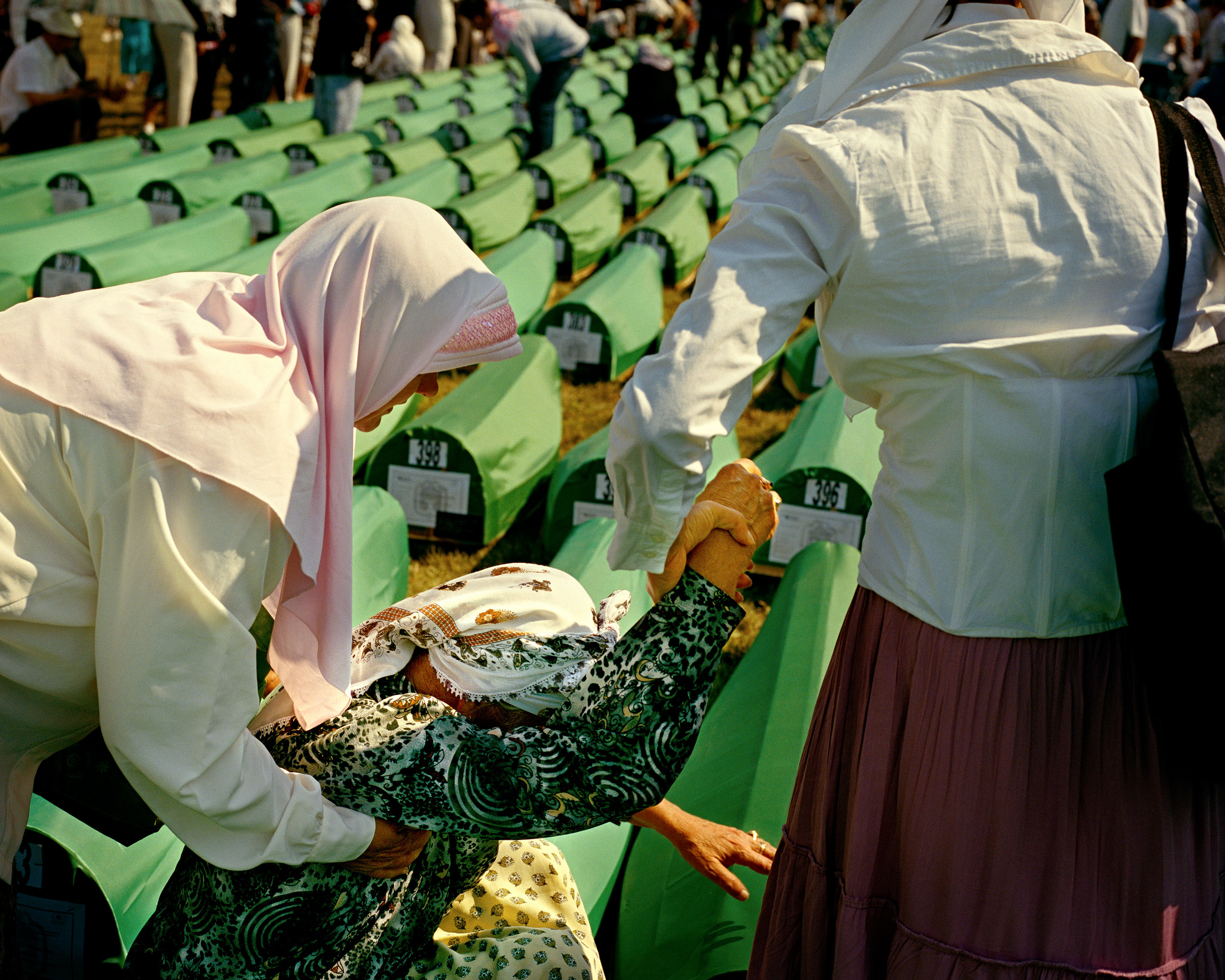 Cemetery in Potocari, Bosnia and Herzegovina                               , 16th anniversary of the Srebrenica Massacre, 2011                               Women grieve the remains of their relatives killed by Serbian military units  during the Bosnian War. Identified human remains from the mass graves are buried every year on the anniversary of the massacre.