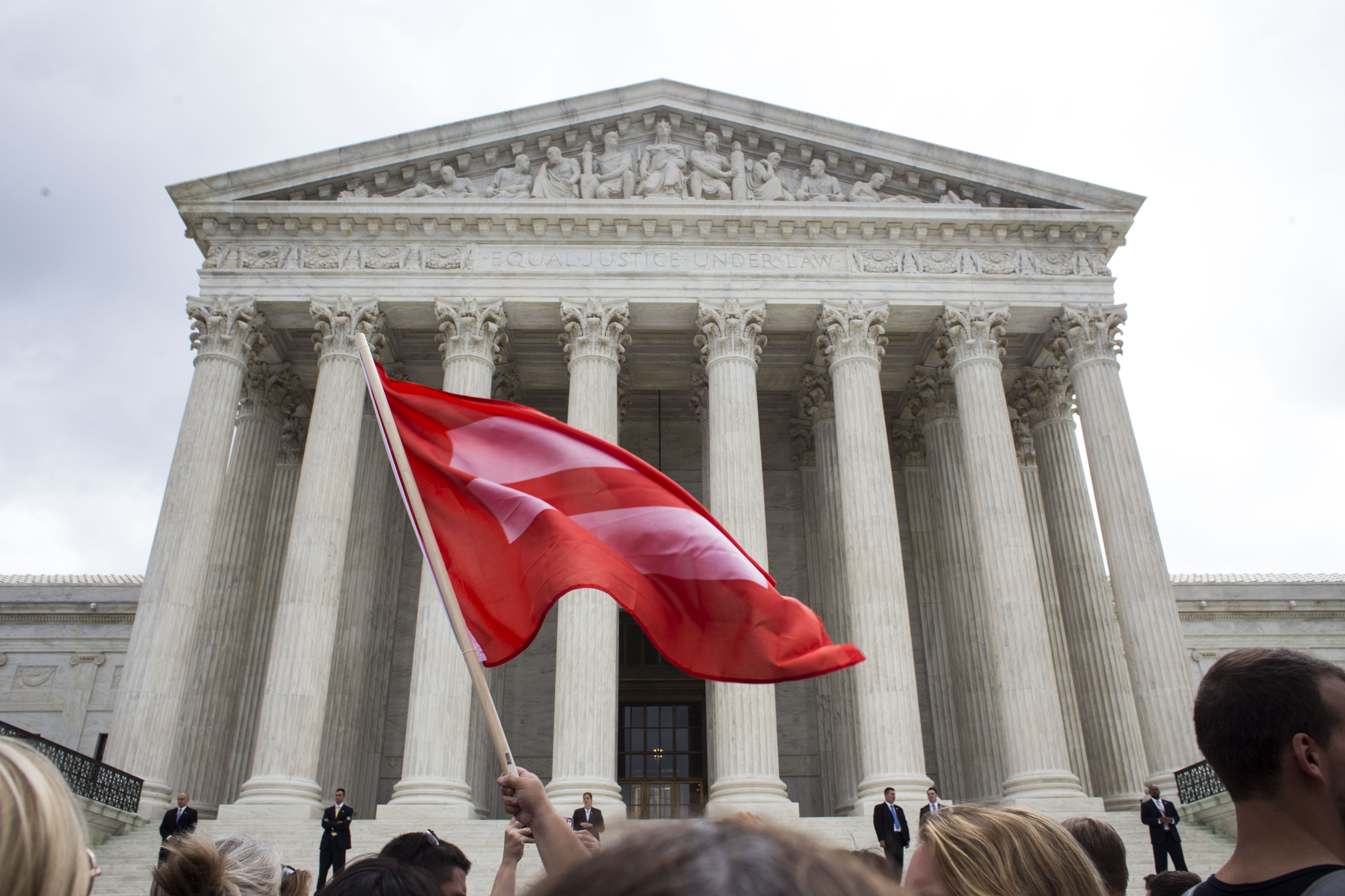A man waves a marriage equality flag in front of The Supreme Court following the decision in favor of same-sex marriage in Washington, DC, on June 26, 2015.
