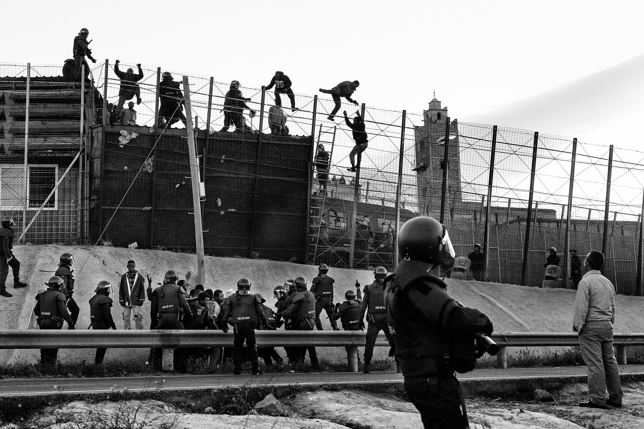 Sub-Saharan migrants  try to cross the border fence between Morocco and Melilla in 2014.
