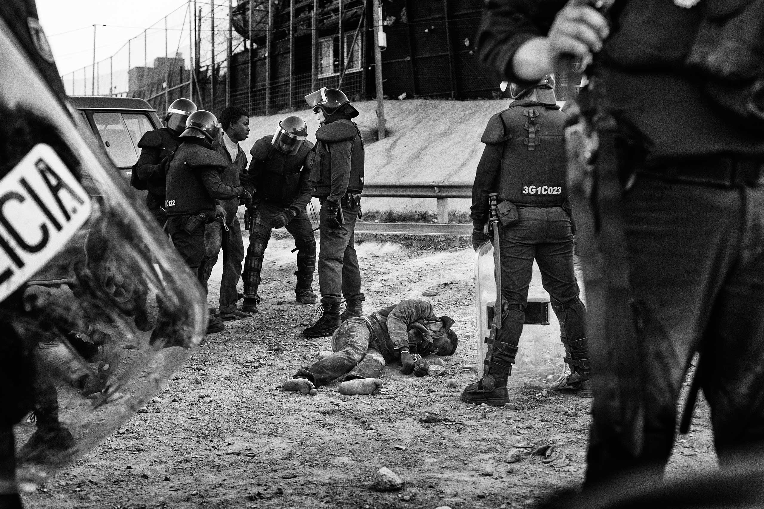 A Sub-Saharan migrant lays on the ground after a clash with the anti-riot police in Melilla in 2014.