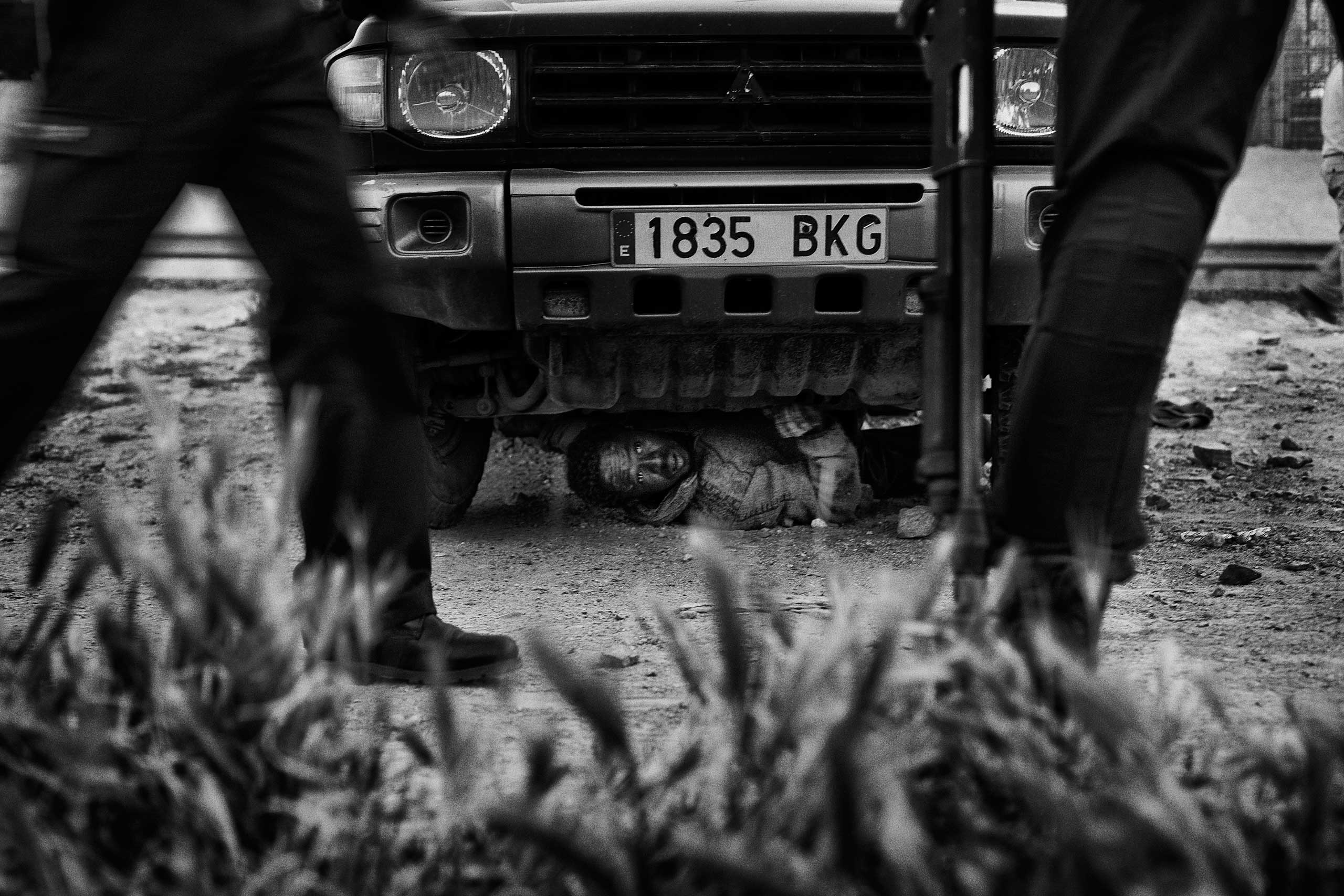 A Sub-Saharan migrant hides under a vehicle trying to avoid expatriation by the Guardia Civil in Melilla in 2014.