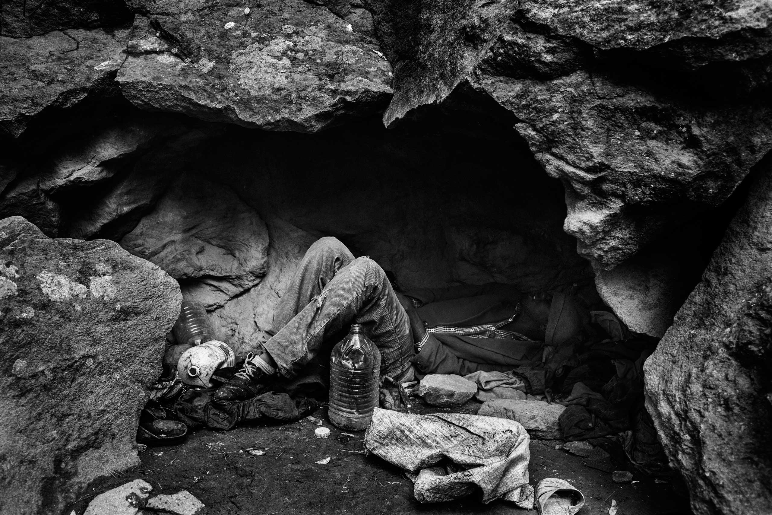 A Malian migrant lays down under a cave used as a shelter in Nador, Morocco in 2012.