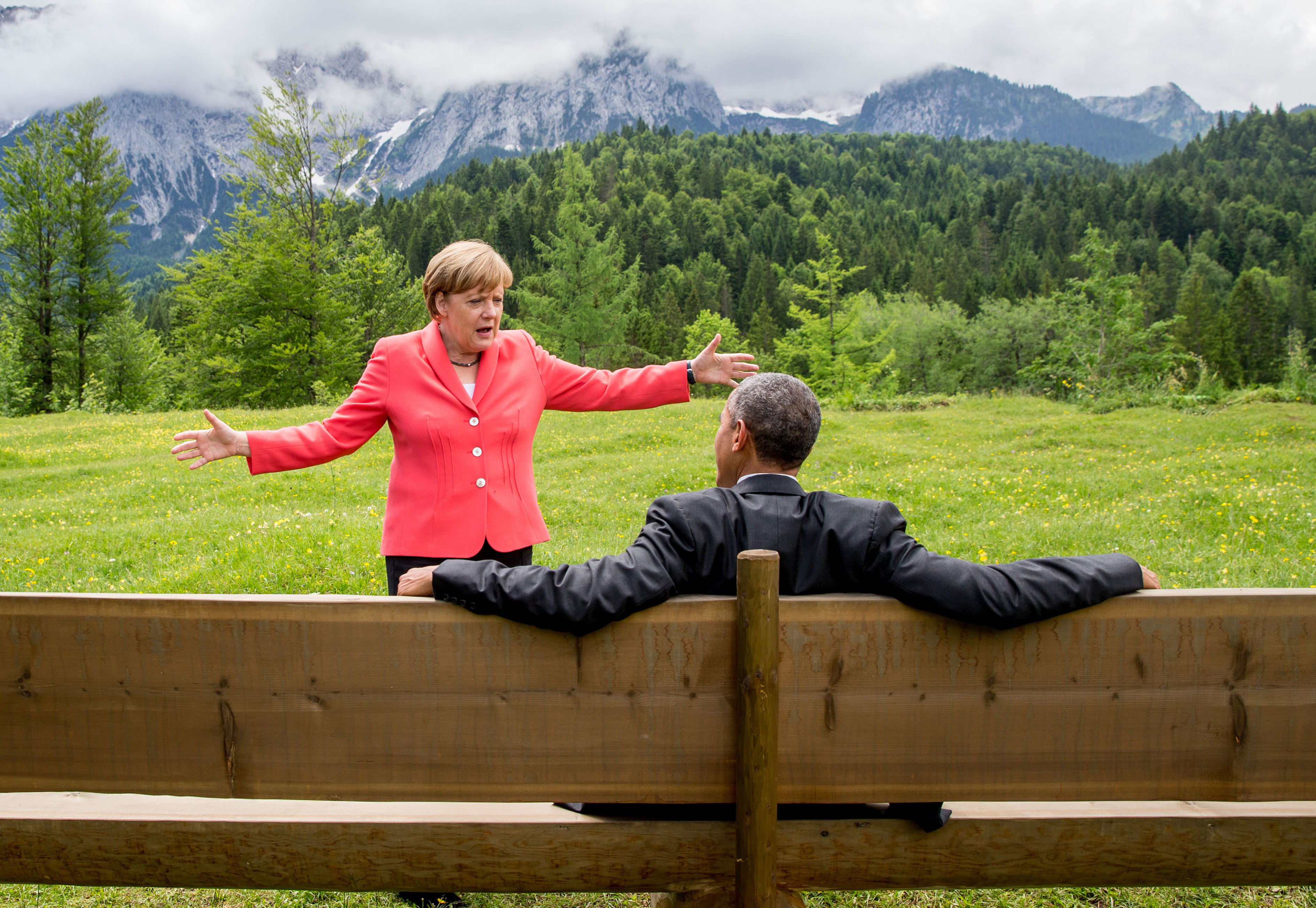 Germany's Chancellor Angela Merkel (L) gestures while chatting with US President Barack Obama sitting on a bench outside the Elmau Castle after a working session of a G7 summit near Garmisch-Partenkirchen, southern Germany, on June 8, 2015.