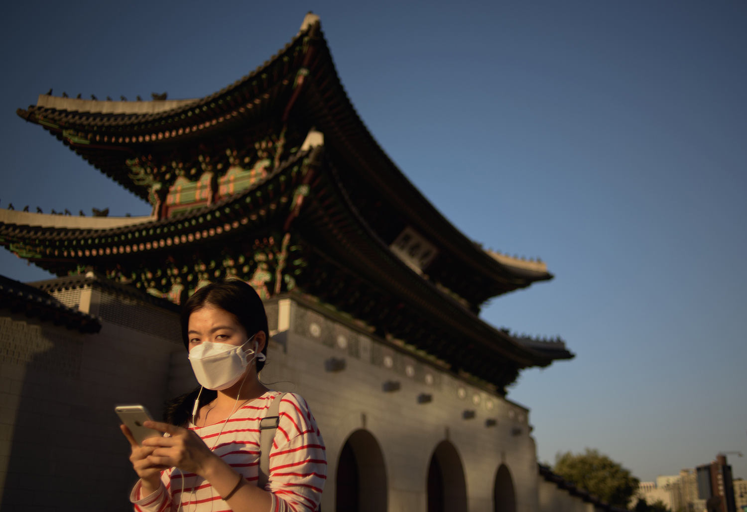 A woman wearing a face mask walks past Gyeongbokgung palace in Seoul on on June 3, 2015