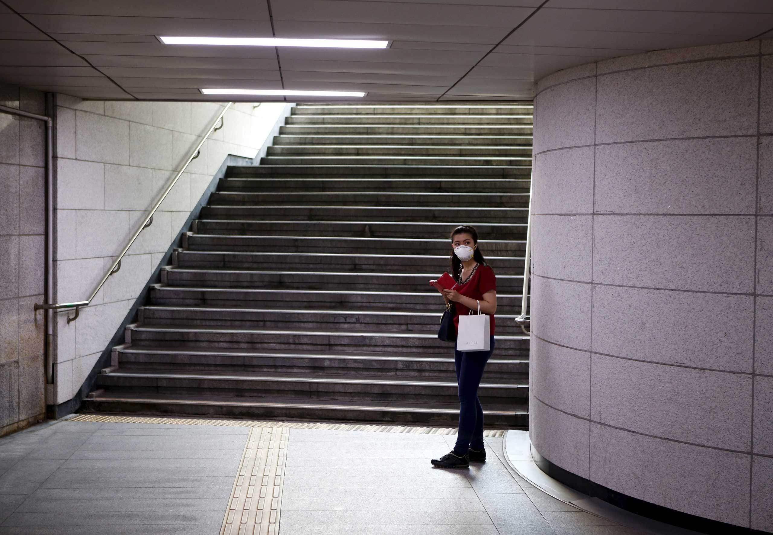 A woman wearing a mask stands in front of the stairs at an underground passageway in central Seoul on  June 12, 2015.