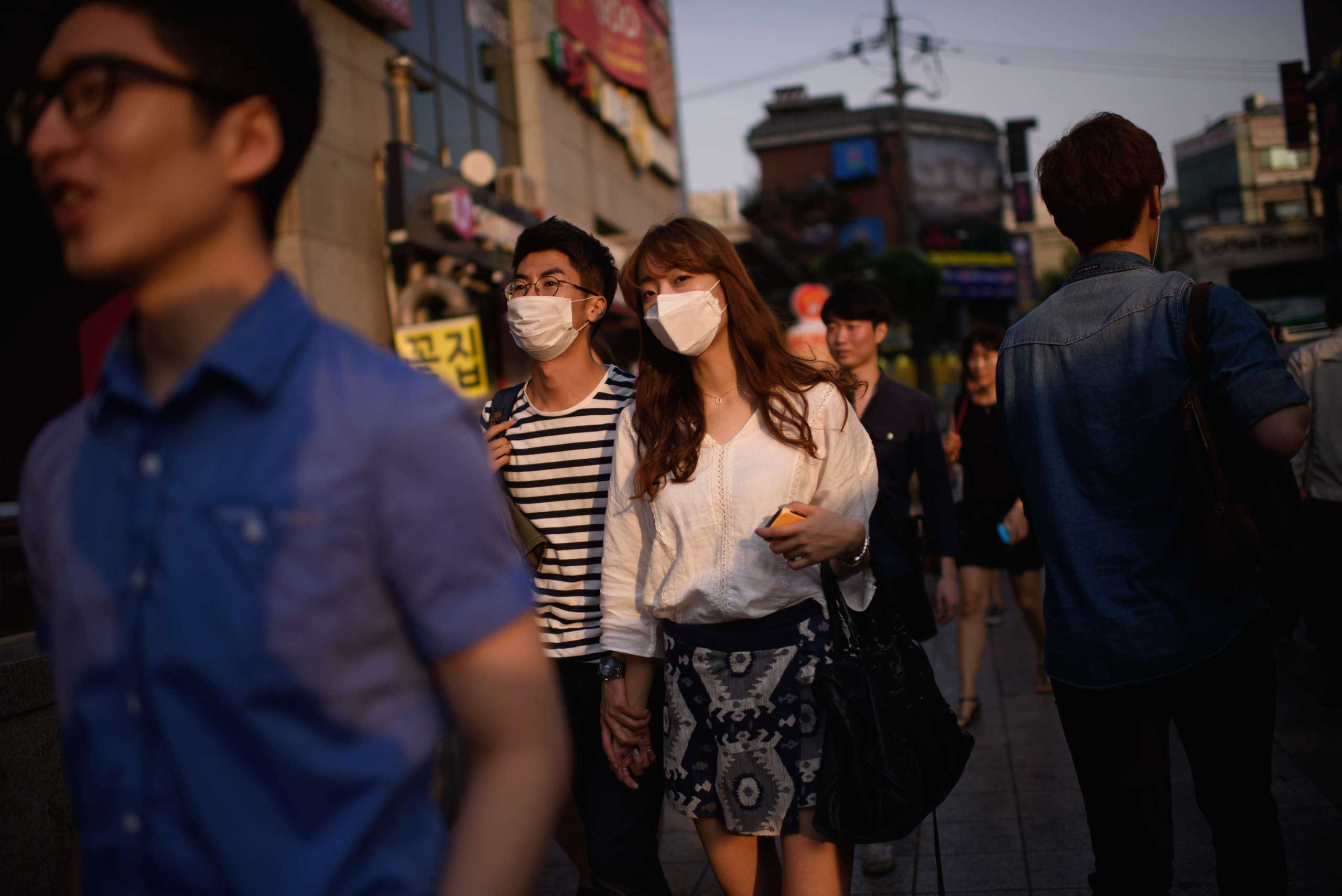 A couple wearing face masks walk on a street in Seoul on June 9, 2015.