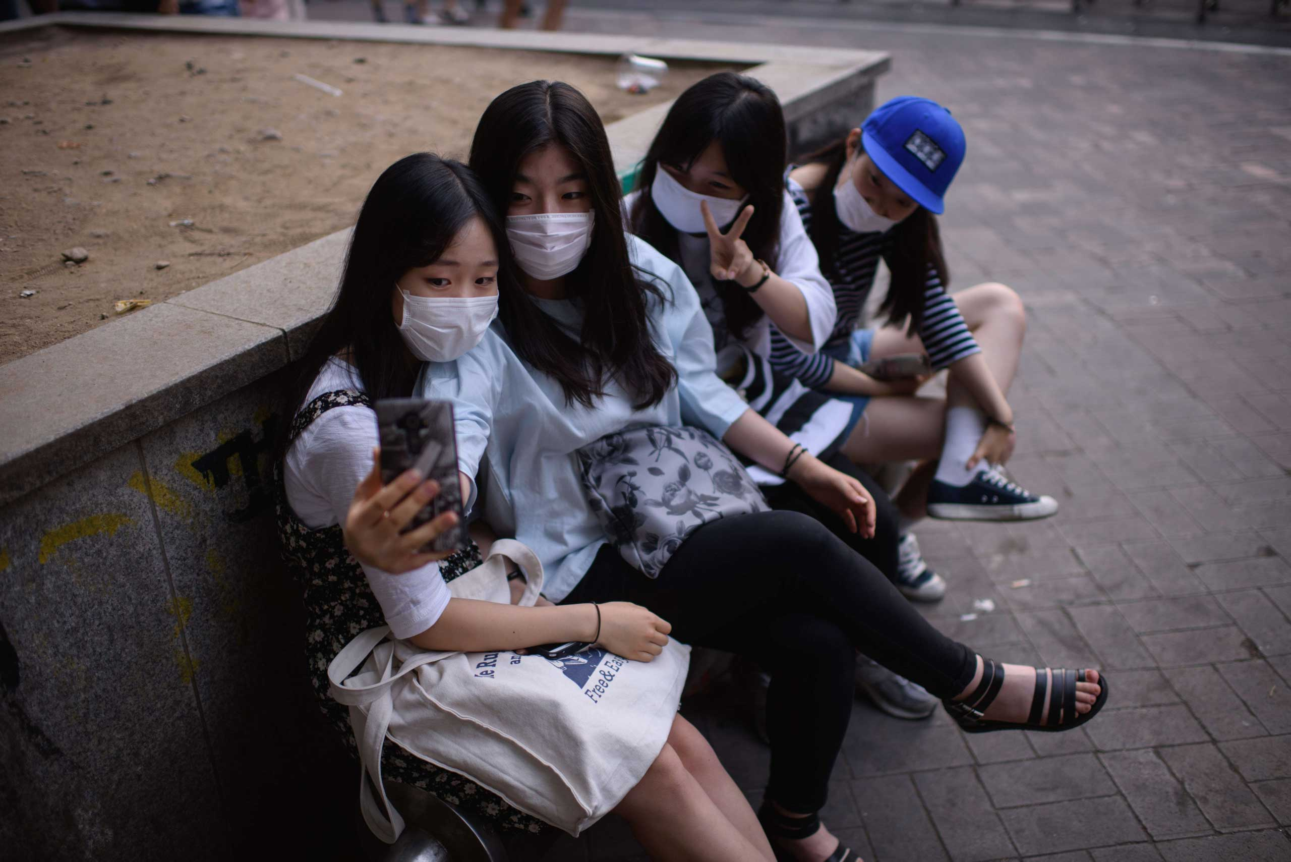 """A group of students wearing face masks pose for a """"selfie"""" as they sit on a street in the popular student area of Hongdae in Seoul on June 7, 2015."""