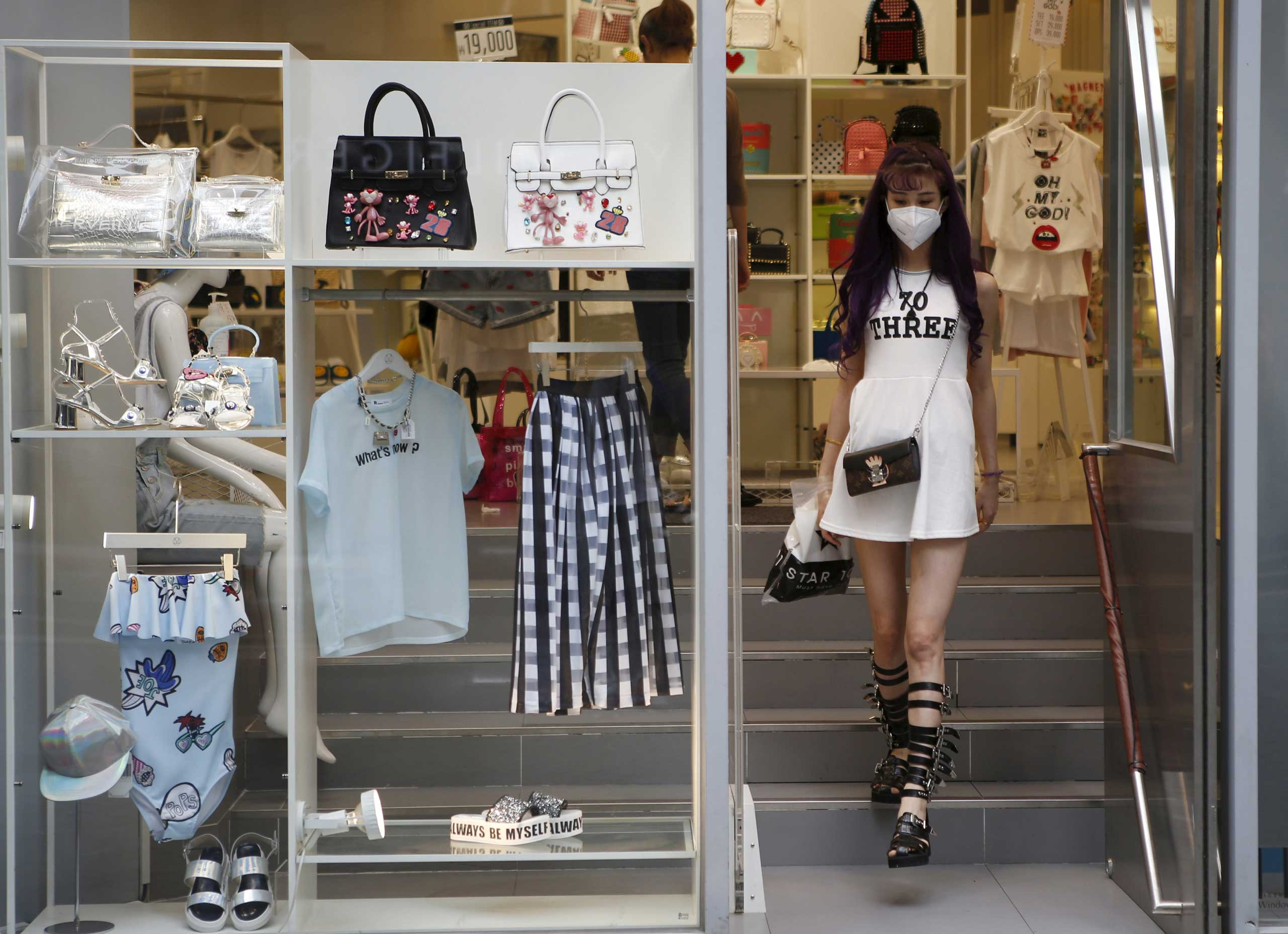 A woman wearing a mask walks out from a clothing shop at Myeongdong shopping district in central Seoul on June 11, 2015.