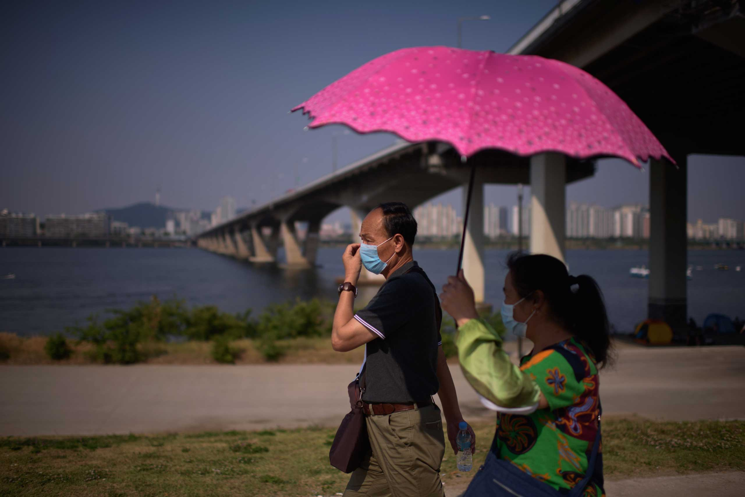 A couple wearing face masks walk beneath the Wonhyo bridge, before the northern city skyline, at Yeouido park in Seoul on June 7, 2015.