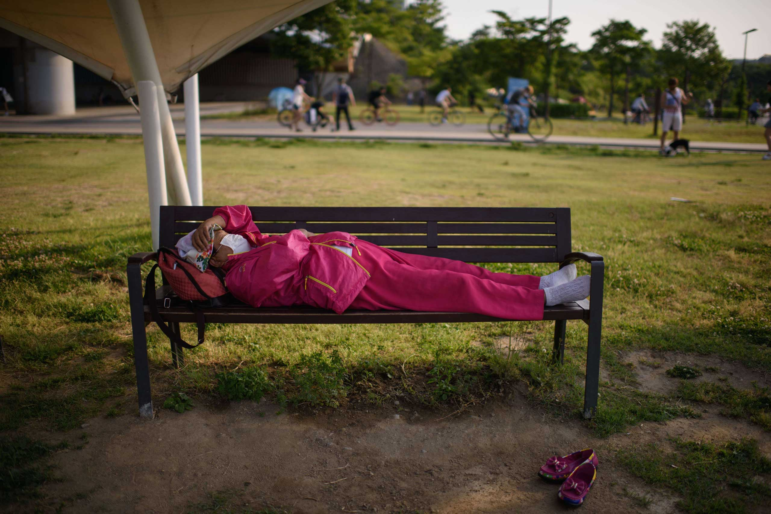 A woman wearing a face mask sleeps on a bench in Yeouido park in Seoul on June 7, 2015.