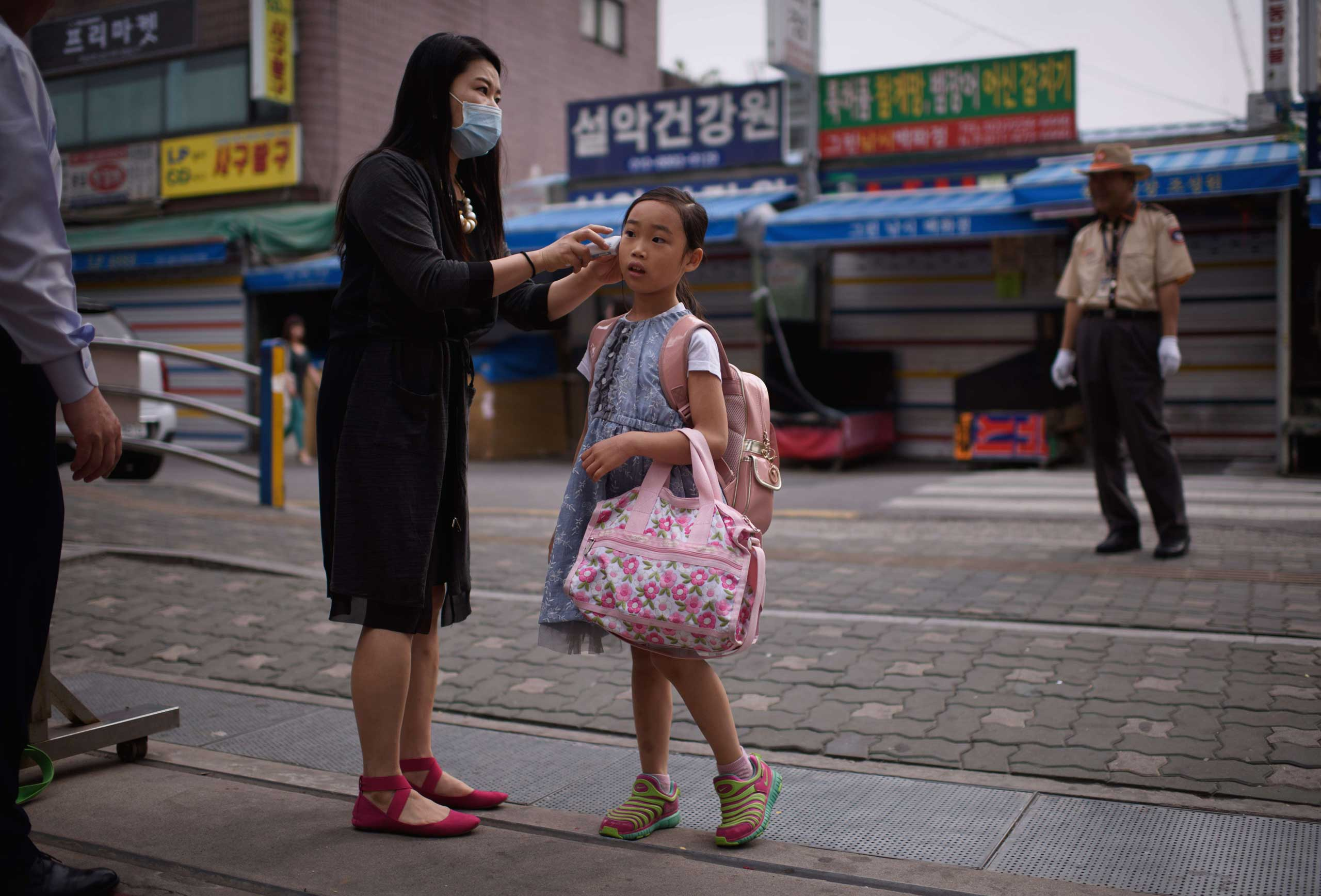 A student has her temperature taken by a teacher outside the Sungshin elementary school in Seoul on June 8, 2015.