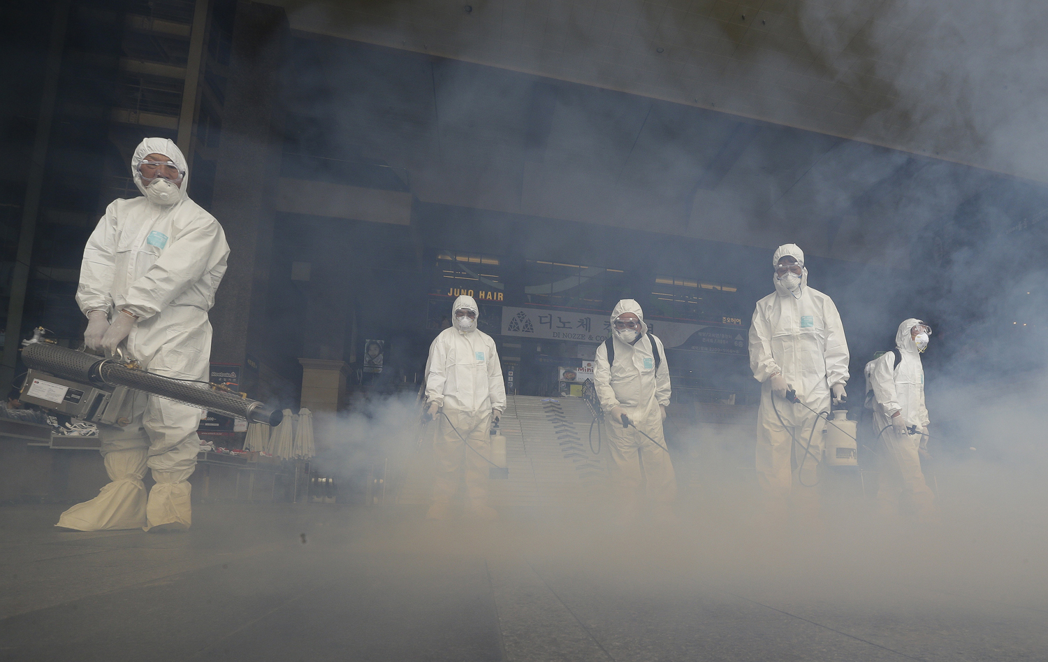 A worker wearing protective gear fumigates to help halt the spread of the MERS virus outside Wangsimni Subway Station in Seoul on June 11, 2015